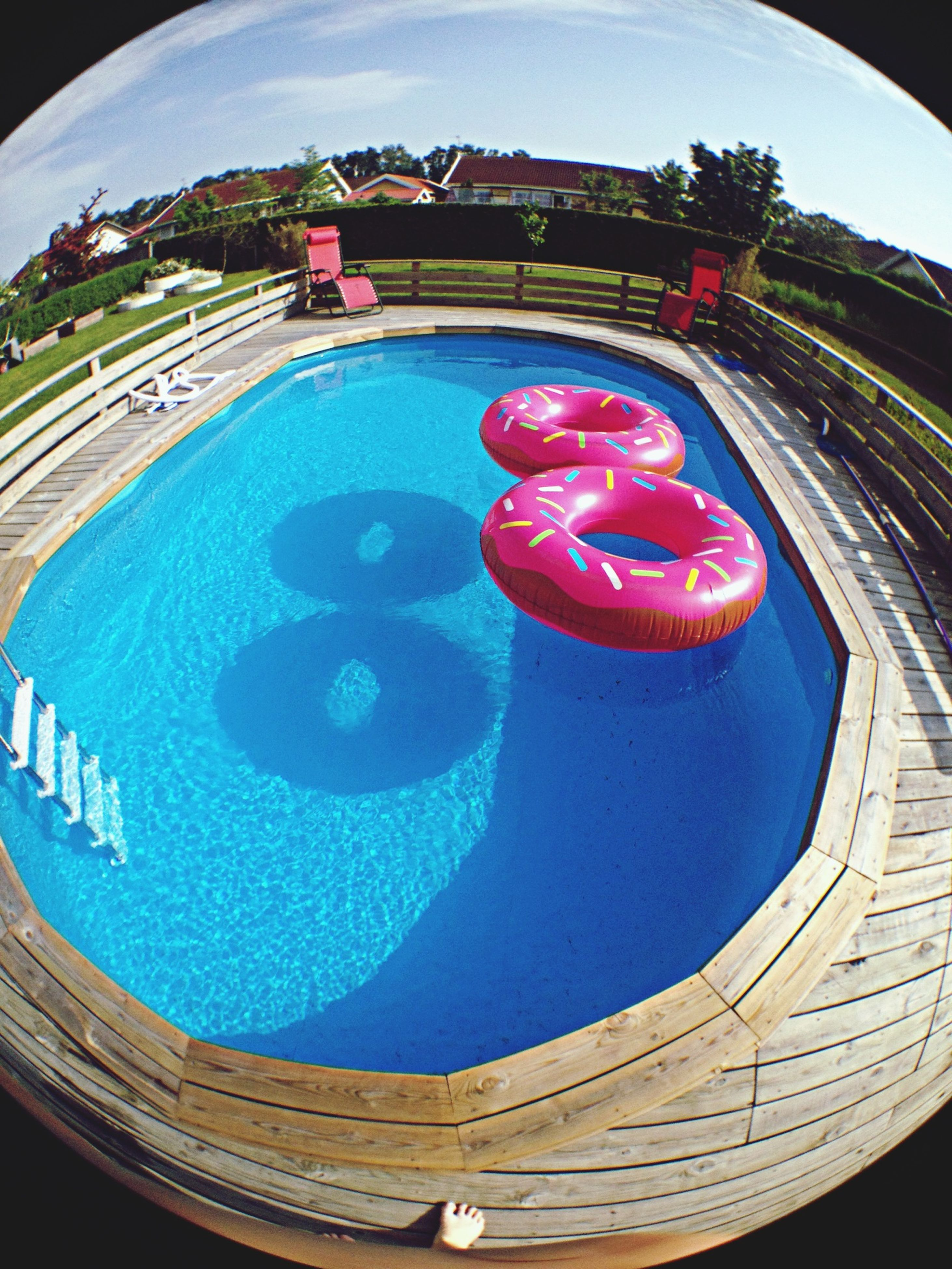 blue, built structure, architecture, circle, fish-eye lens, building exterior, water, multi colored, sky, swimming pool, day, high angle view, outdoors, reflection, no people, nature, part of, sunlight, round, red