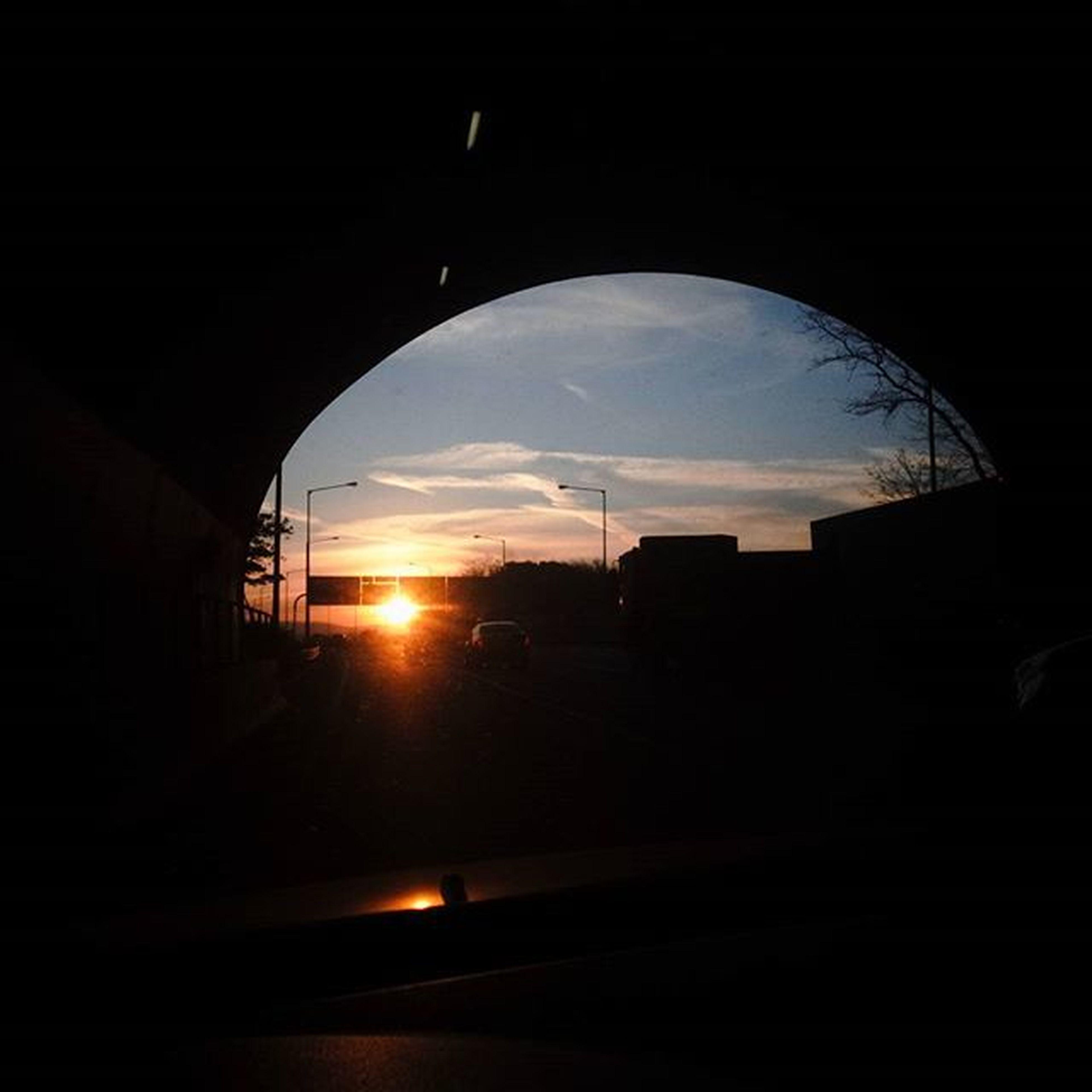 silhouette, built structure, architecture, indoors, sunset, sky, window, arch, dark, sun, building exterior, sunlight, cloud - sky, no people, road, house, building, transportation, glass - material, transparent