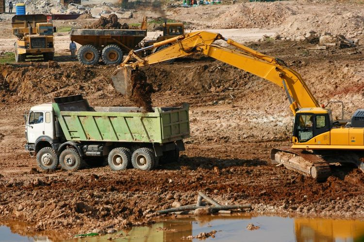 Excavator at work clearing a building site Adult Bulldozer Construction Machinery Construction Site Construction Vehicle Day Digging Dump Truck Earth Mover Industry Land Vehicle Machinery Mud One Person Outdoors People Transportation Working