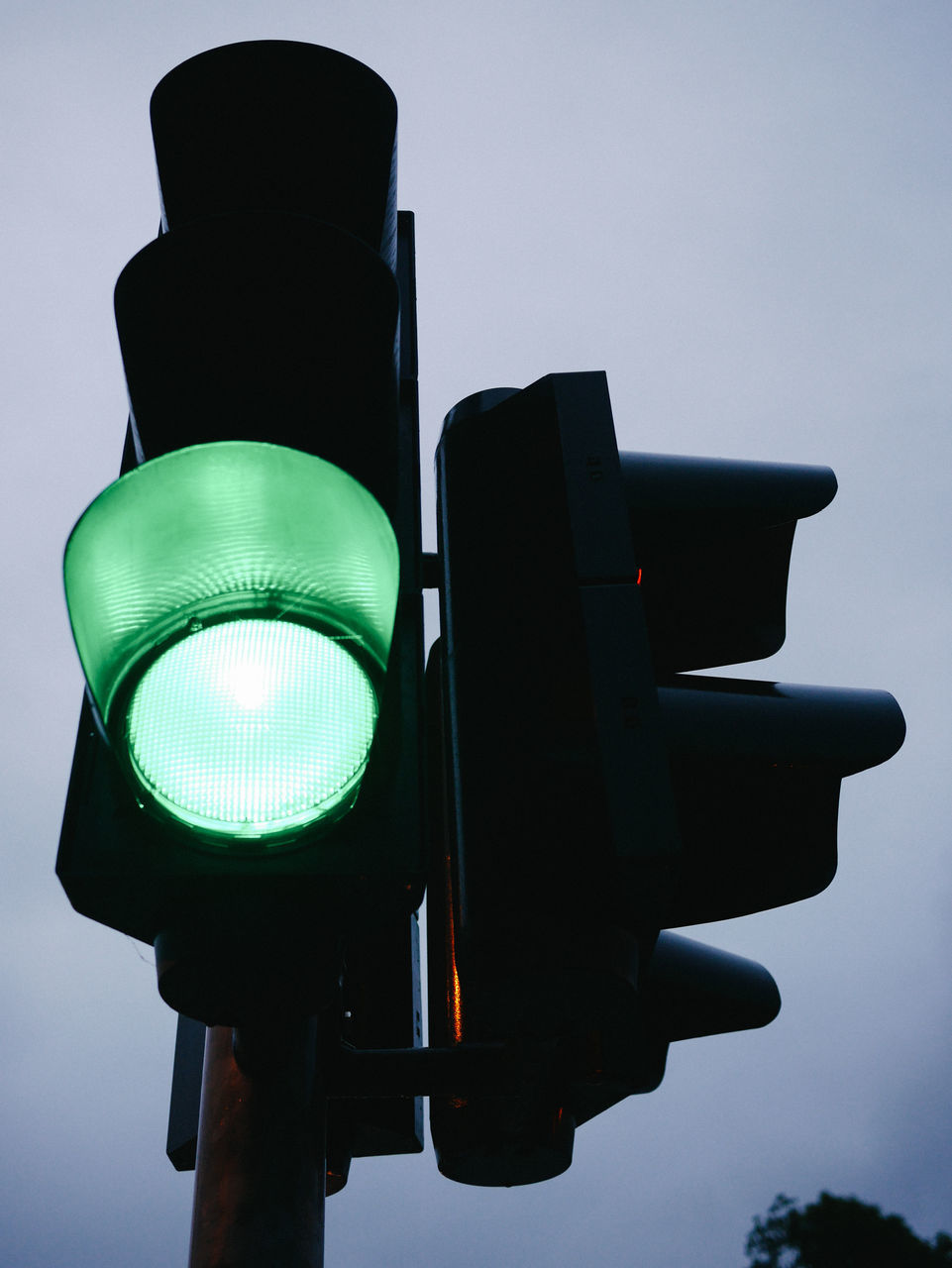 Low Angle View Of Illuminated Green Road Signal Against Sky
