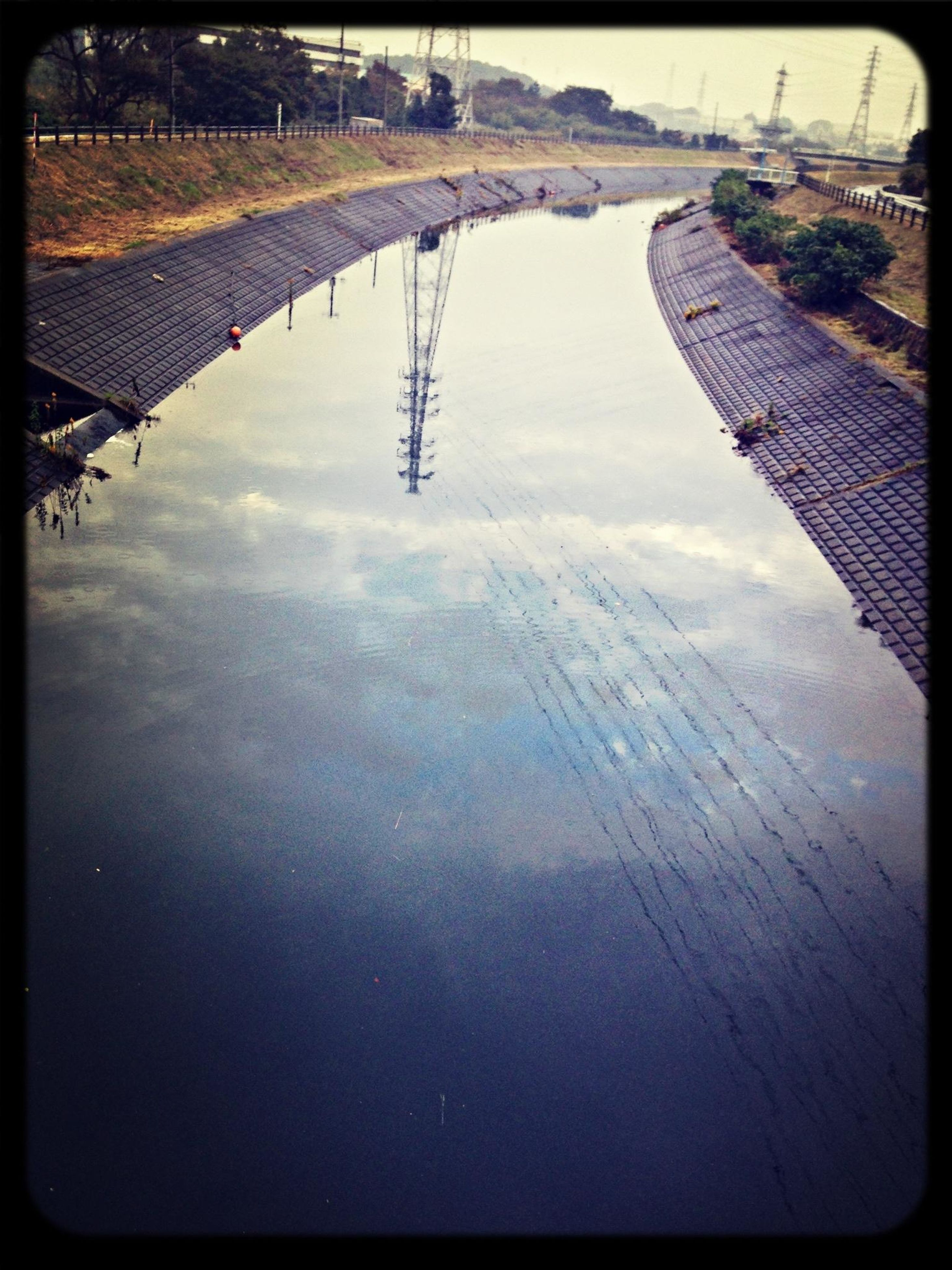 water, reflection, built structure, architecture, river, building exterior, high angle view, transfer print, waterfront, sky, auto post production filter, city, lake, transportation, outdoors, day, tree, cloud - sky, bridge - man made structure, nature