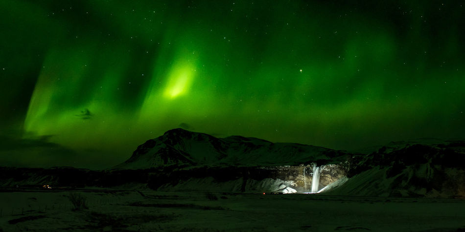 """Seljalandsfoss under a green sky. Installed lights make Seljalandsfoss clearly visible from the main road. The massive waterfall looked small under the green heavens, dancing overhead. (Nikon D810 24-70mm f/2.8 ƒ/4 24mm 5"""" iso 1600) Aurora Polaris Copy Space Green Color Iceland Illuminated Landscape Landscape_Collection Long Exposure Mountain Nature Night No People Outdoors Scandinavia Scenics Sky Tranquility Water Waterfall"""