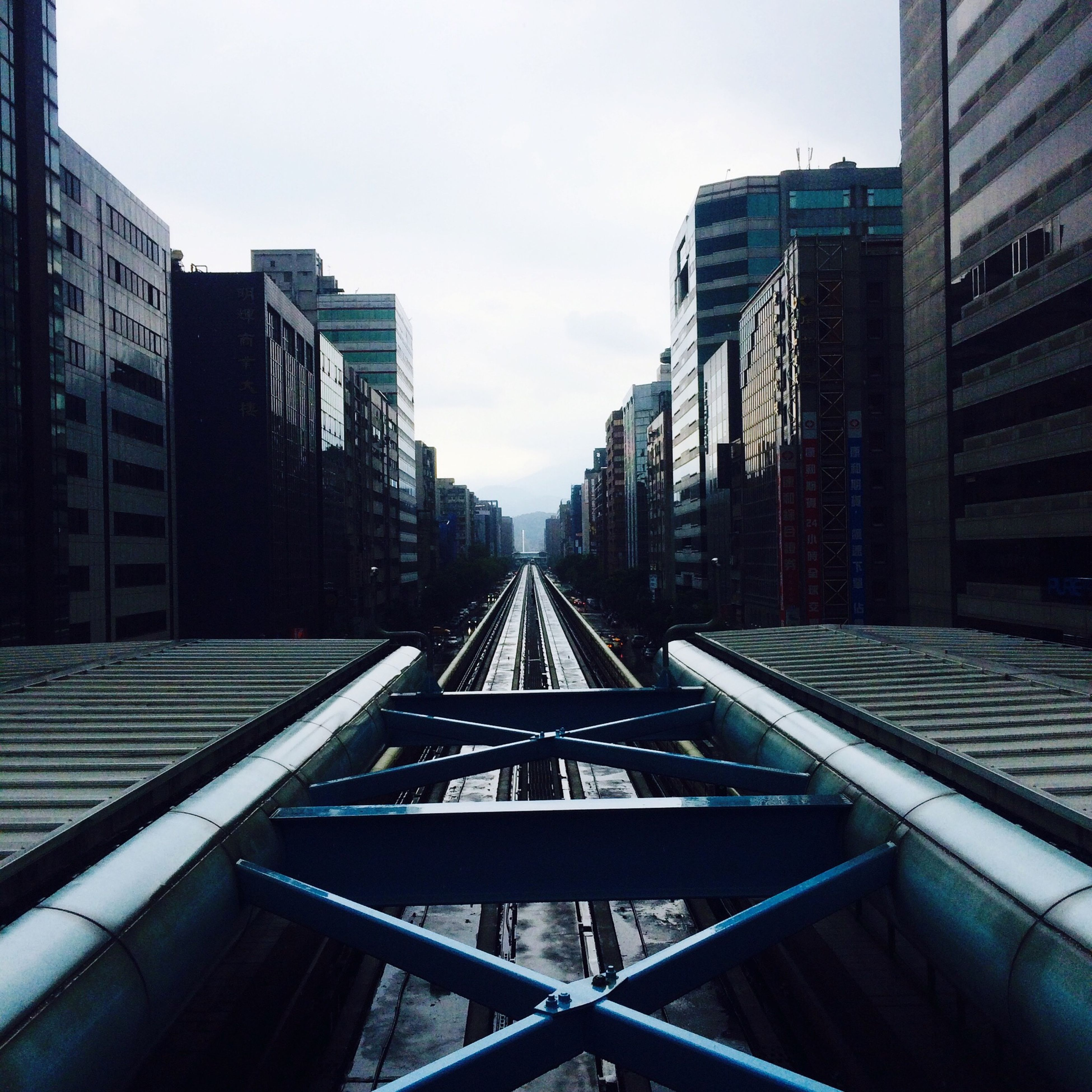 architecture, built structure, railroad track, the way forward, diminishing perspective, building exterior, vanishing point, rail transportation, transportation, sky, city, public transportation, day, outdoors, no people, railroad station, railway track, connection, building, long
