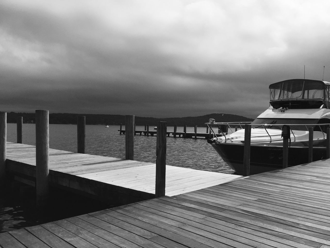 Wooden Jetty At Calm Sea Against Cloudy Sky
