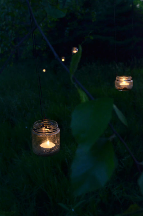 illuminated upcycled glass jars handcrafted hanging lanterns with tea candles Candlelight Candles Close-up Craft Garden Lantern Glass Jars Hanging Hanging Lanterns Illuminated Lantern Nature Night Night Lights No People Outdoors Tea Candle Upcycled