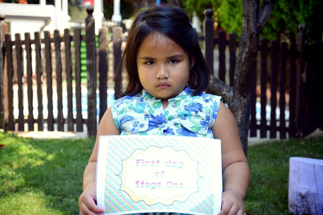 Portrait Of Cute Angry Girl Holding Message In Yard