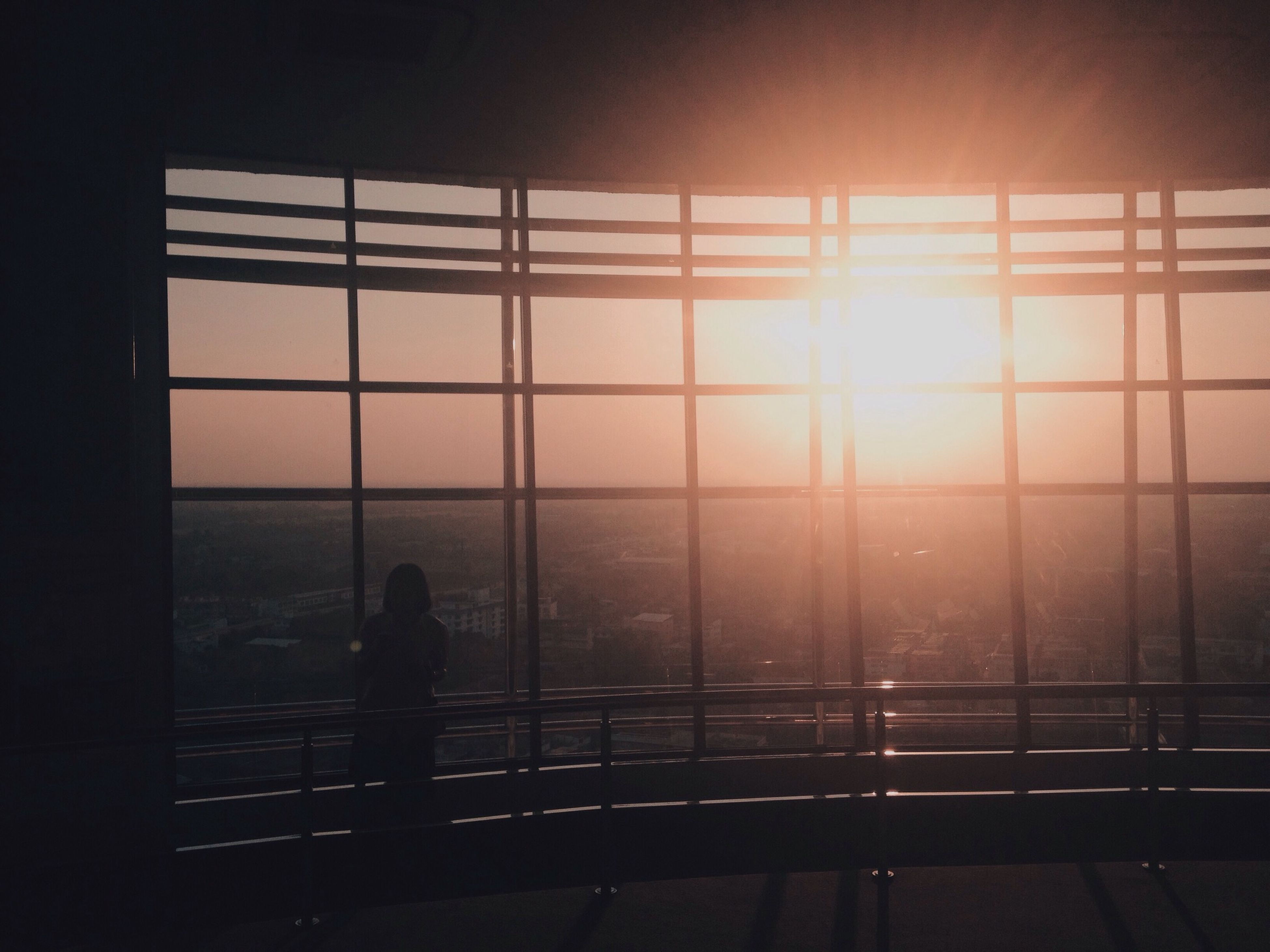 window, indoors, glass - material, sunset, transparent, sun, sunlight, railing, sky, water, reflection, horizon over water, built structure, sea, architecture, silhouette, glass, nature, sunbeam, lens flare