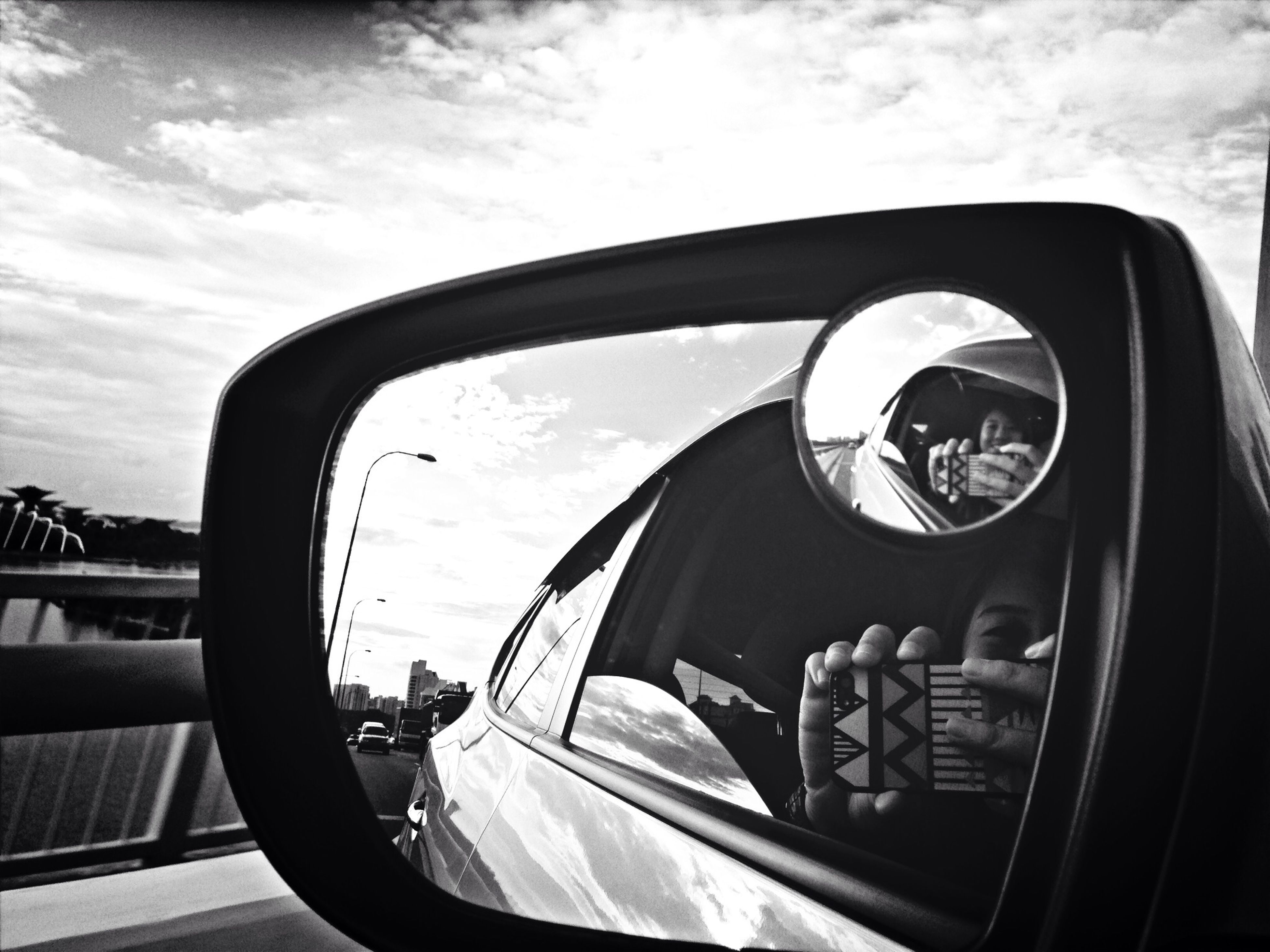transportation, mode of transport, land vehicle, car, side-view mirror, sky, part of, car interior, reflection, road, vehicle interior, cropped, travel, vehicle part, glass - material, street, vehicle, cloud - sky, windshield, stationary