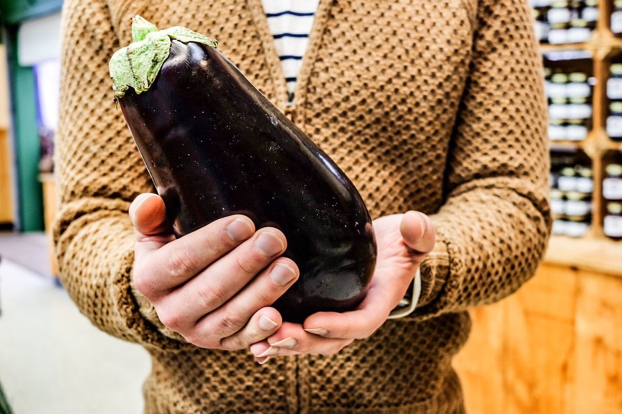 Midsection Of Man Holding Eggplant