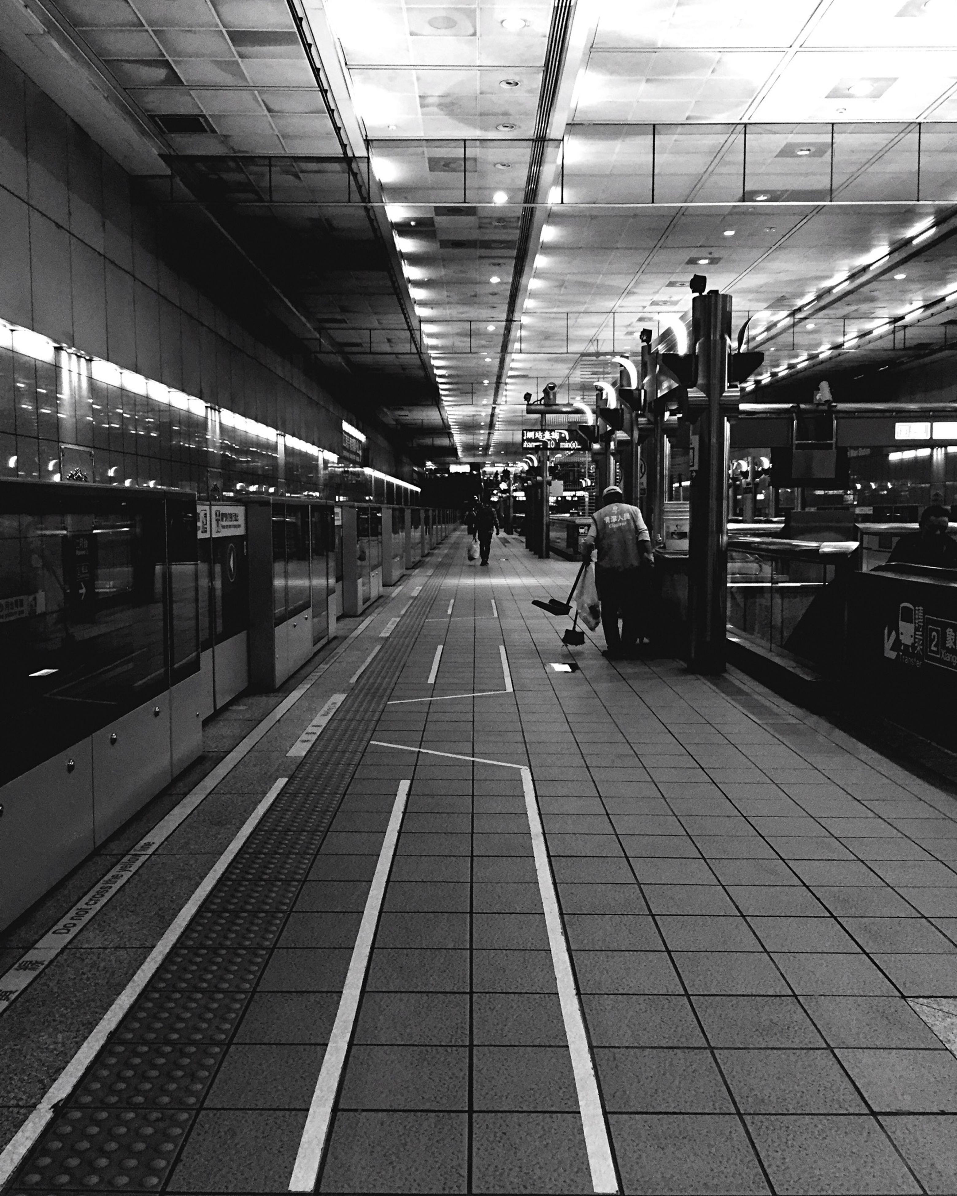 indoors, ceiling, transportation, men, railroad station platform, the way forward, railroad station, lifestyles, incidental people, travel, person, walking, airport, public transportation, rail transportation, railroad track, diminishing perspective, built structure, tiled floor