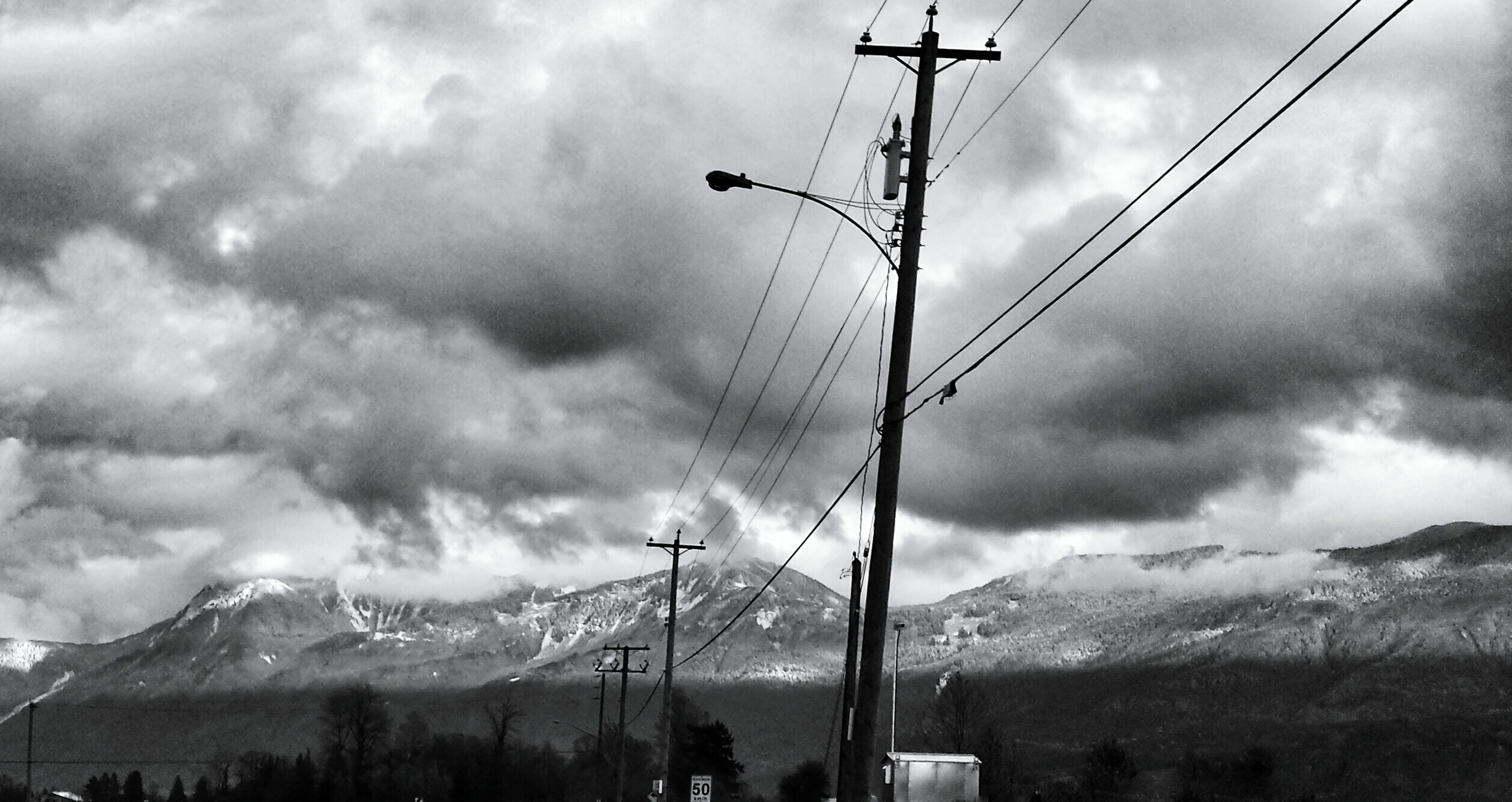 power line, electricity pylon, mountain, electricity, sky, power supply, cloud - sky, cable, connection, cloudy, fuel and power generation, weather, mountain range, low angle view, technology, scenics, overhead cable car, landscape, tranquility, nature