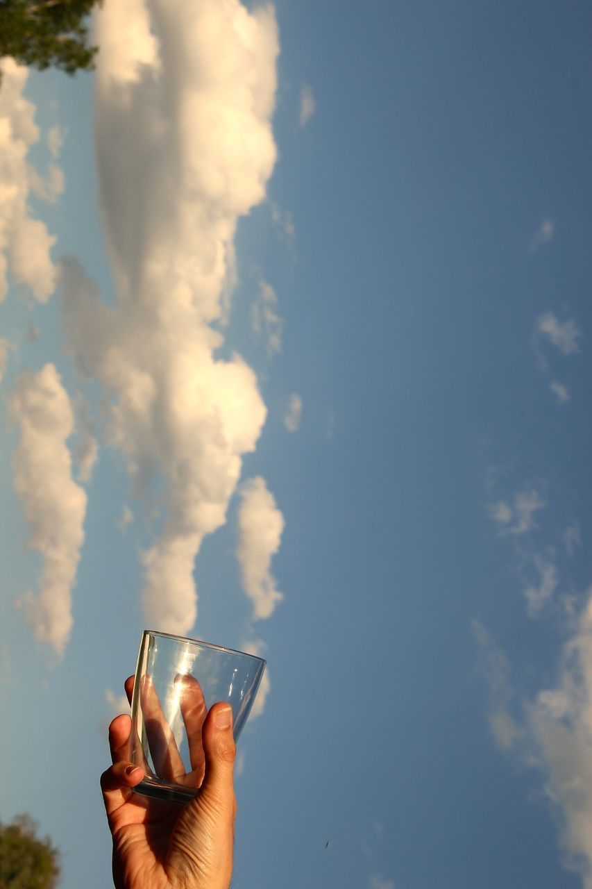 Optical Illusion Of Person Collecting Clouds In Glass