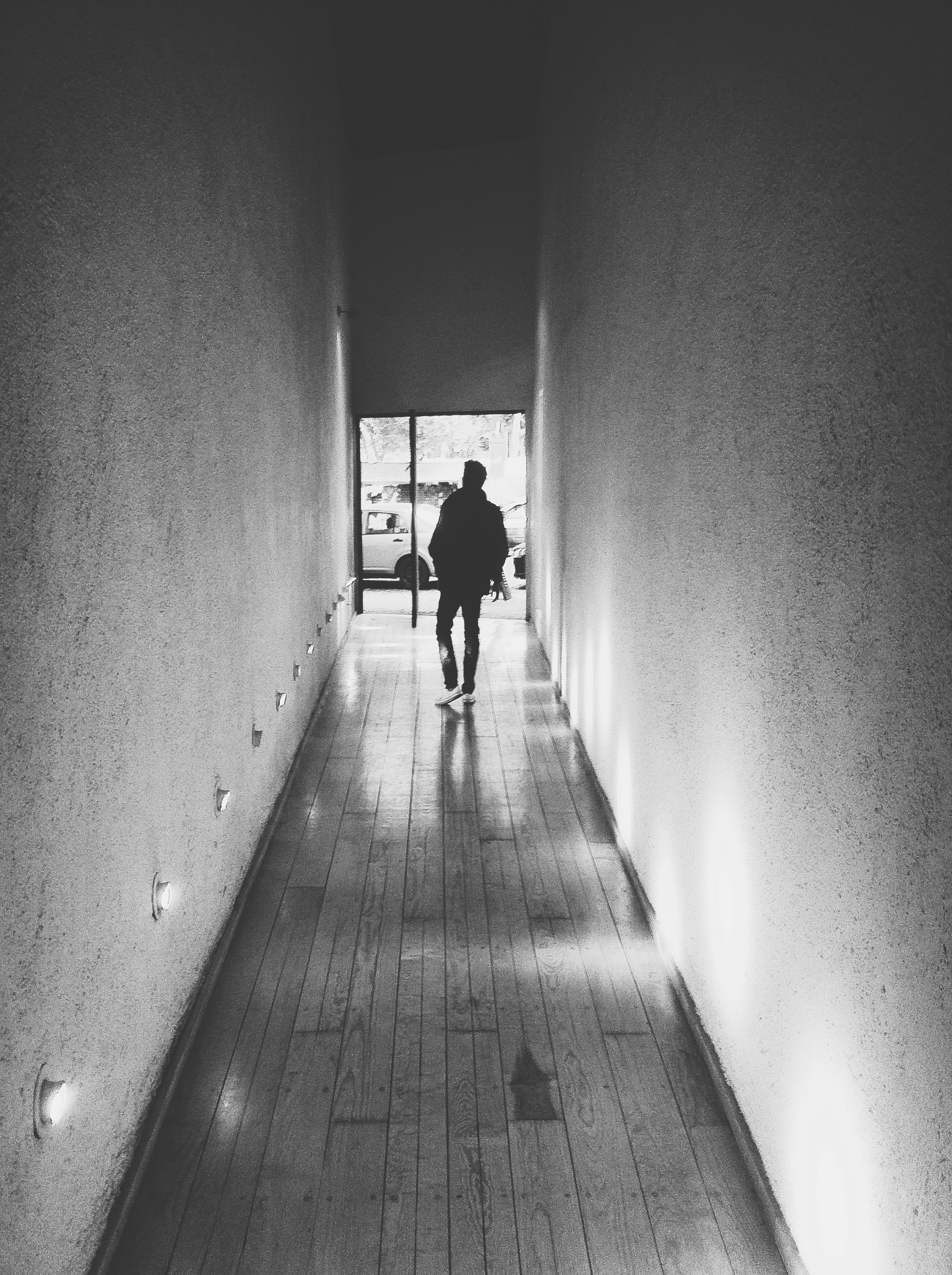 architecture, indoors, built structure, full length, wall - building feature, men, walking, the way forward, lifestyles, rear view, wall, building, leisure activity, building exterior, silhouette, day, unrecognizable person, illuminated