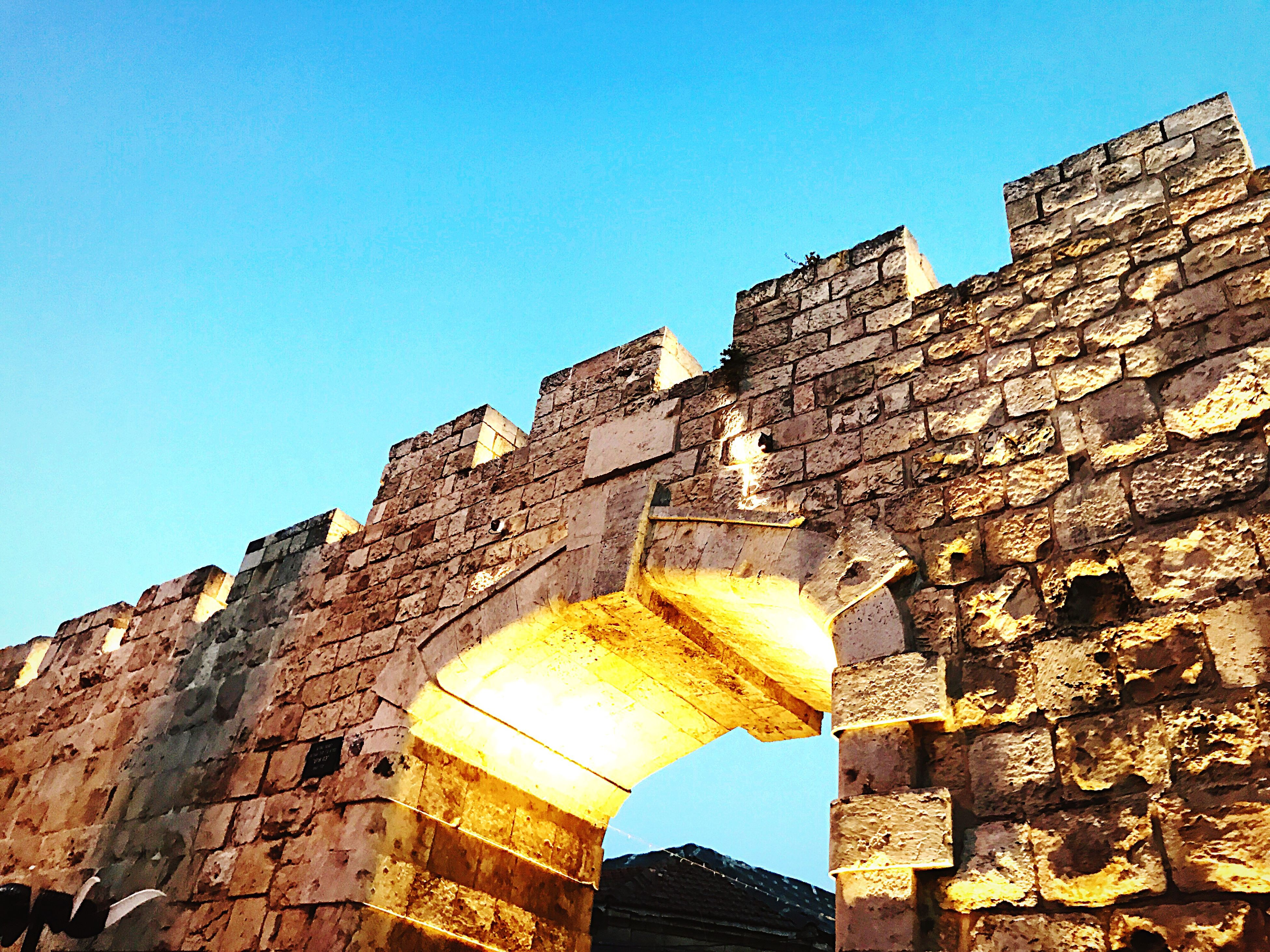 architecture, built structure, history, old ruin, building exterior, low angle view, old, ancient, clear sky, archaeology, sunlight, ancient civilization, the past, brick wall, day, no people, travel destinations, outdoors, blue, sky, city
