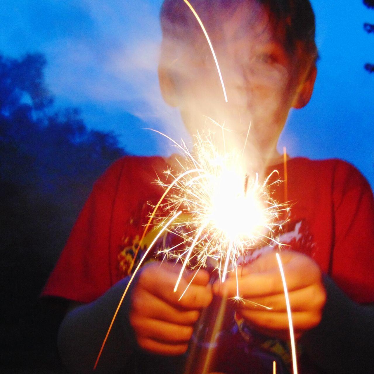 Boy With Illuminated Sparkler Against Sky At Dusk