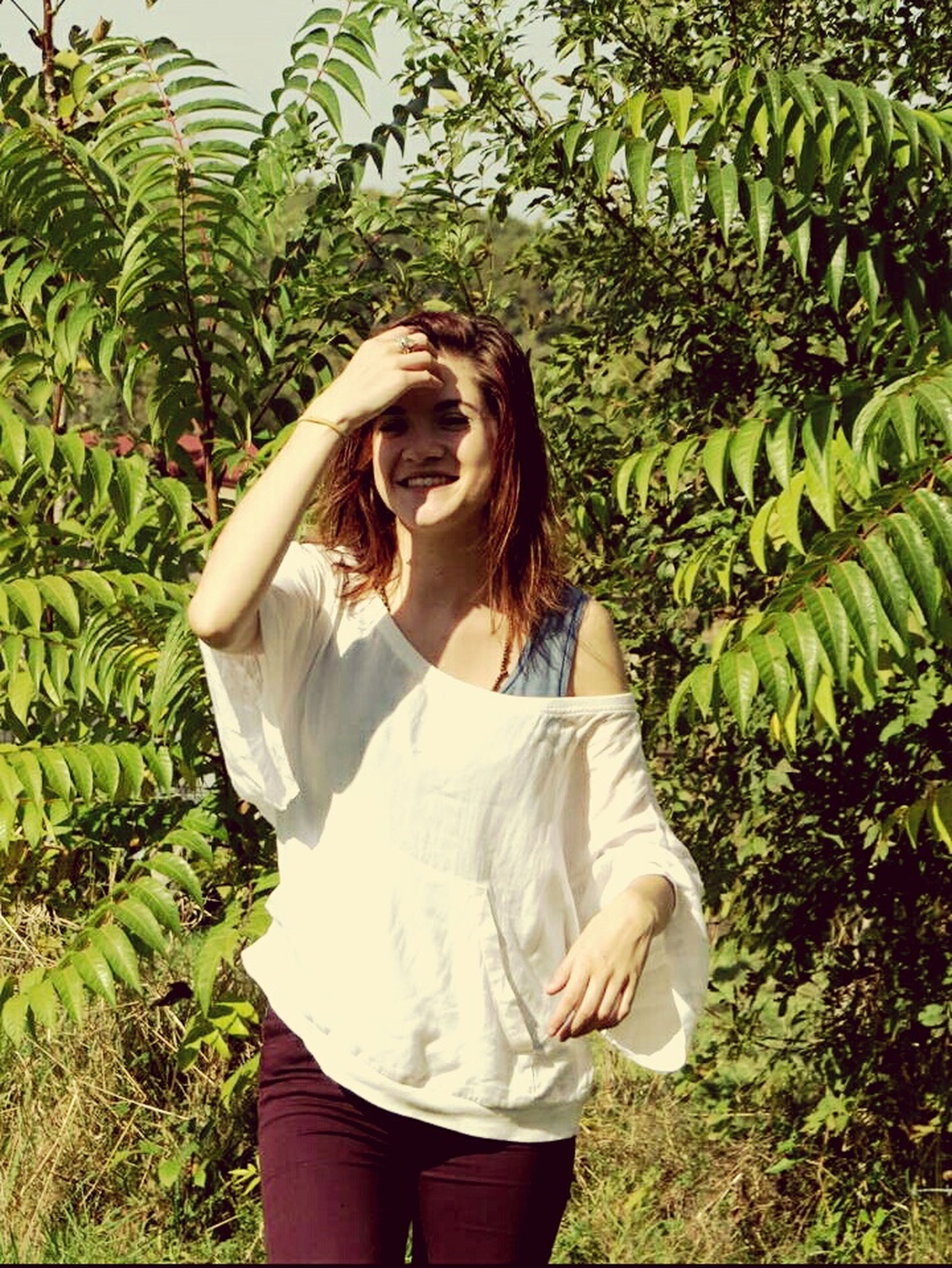casual clothing, lifestyles, young adult, young women, long hair, person, standing, leisure activity, tree, three quarter length, growth, grass, plant, green color, waist up, field, nature
