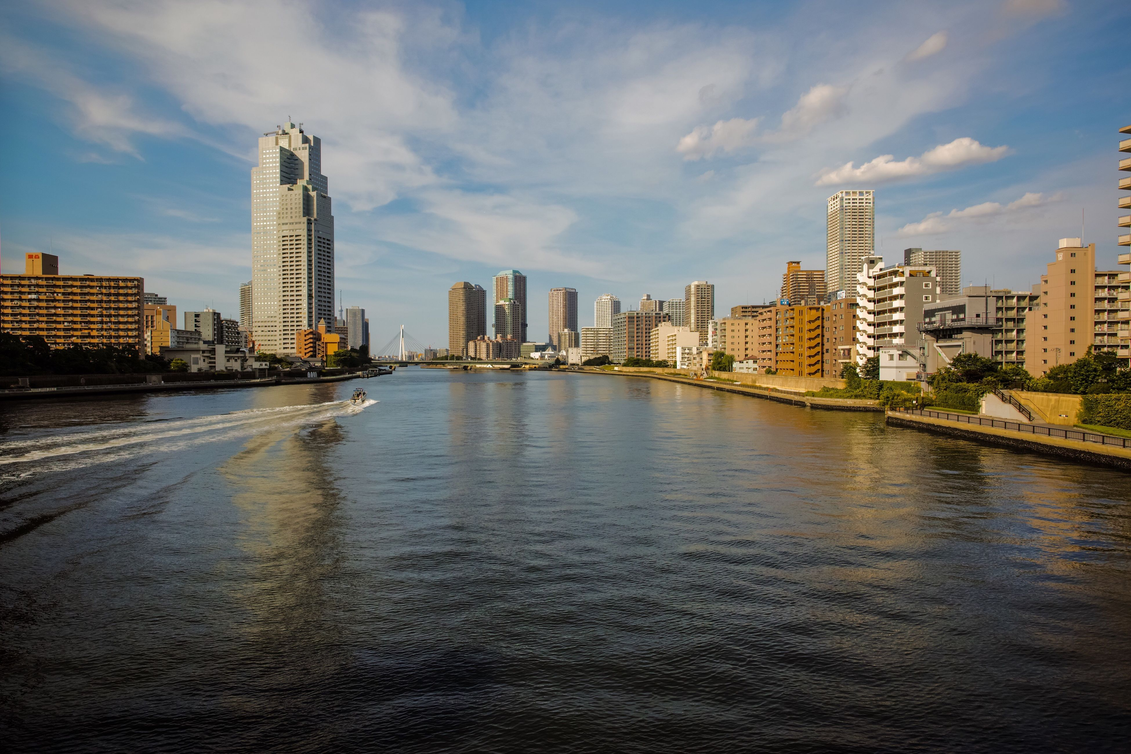 architecture, skyscraper, built structure, building exterior, water, tall - high, city, sky, waterfront, urban skyline, cityscape, tower, cloud - sky, modern, river, travel destinations, downtown district, outdoors, no people, day, nature