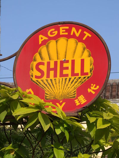 Ancient Shell Sign Blue Sky Capital Letter Close-up Communication Composition Day Hoi An Information Information Sign Leaf Low Angle View Non-western Script Old Outdoor Photography Outdoors Plant Red And Yellow Red, Yellow And Green Road Sign Shell Petroleum Sign Text Vietnam Western Script Yellow