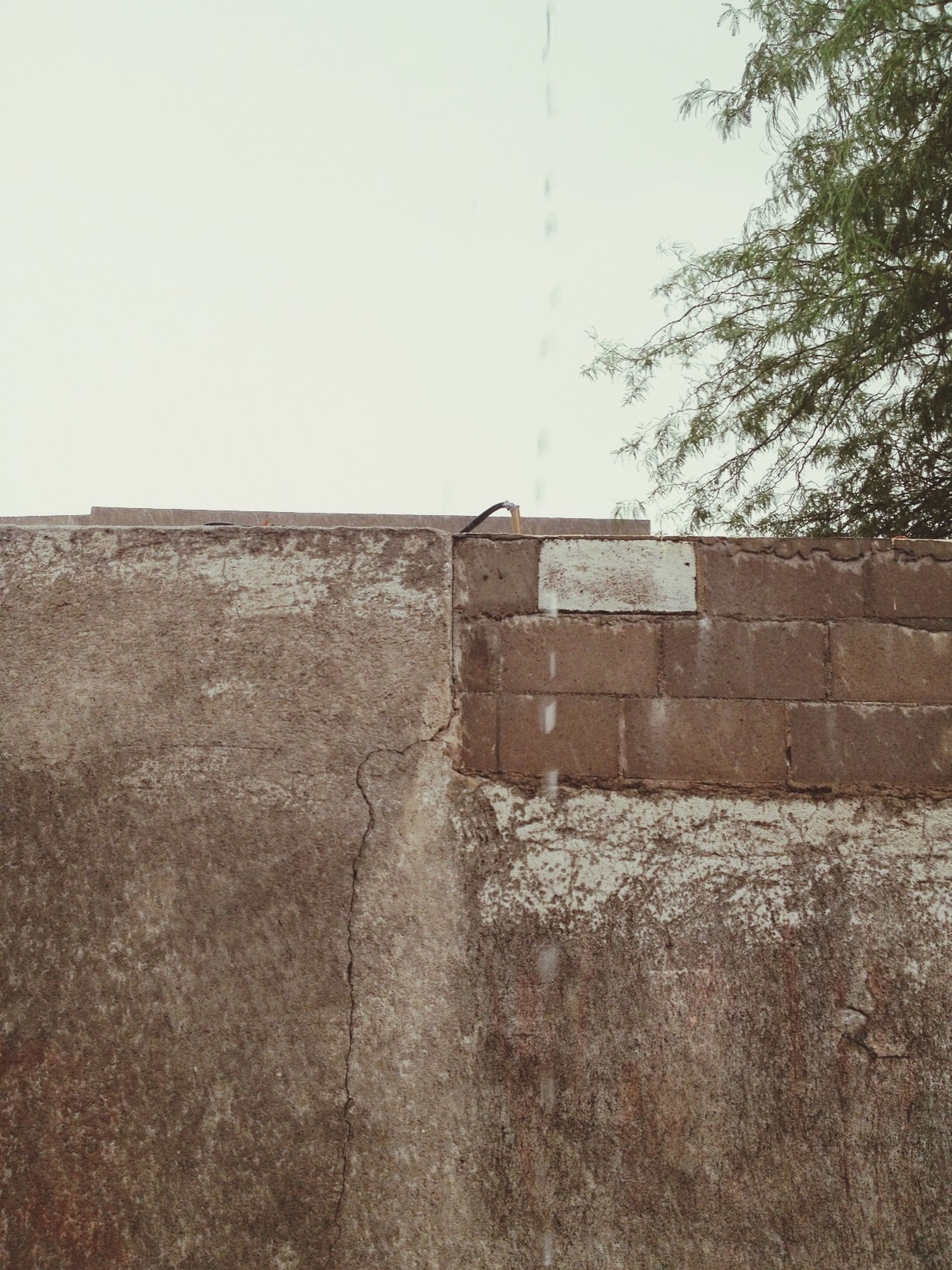 architecture, built structure, building exterior, wall - building feature, clear sky, stone wall, old, house, abandoned, wall, copy space, day, brick wall, damaged, no people, weathered, outdoors, sky, building, obsolete