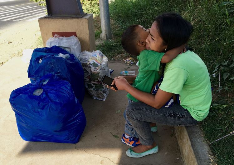 A young boy embraces his mother while waiting for public transportation in Tagaytay, south of Manila. Mother And Son Mother And Child Warm Embrace Tight Embrace Affection Touching Scene