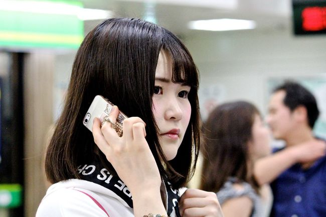 Young woman on a phone call whilst waiting for a train in Shibuya station, Tokyo, Japan. Beauty Black Hair Close-up Focus On Foreground Headshot Innocence Japan Person Photojournalism Streetphotography Tokyo Young Adult Young Women