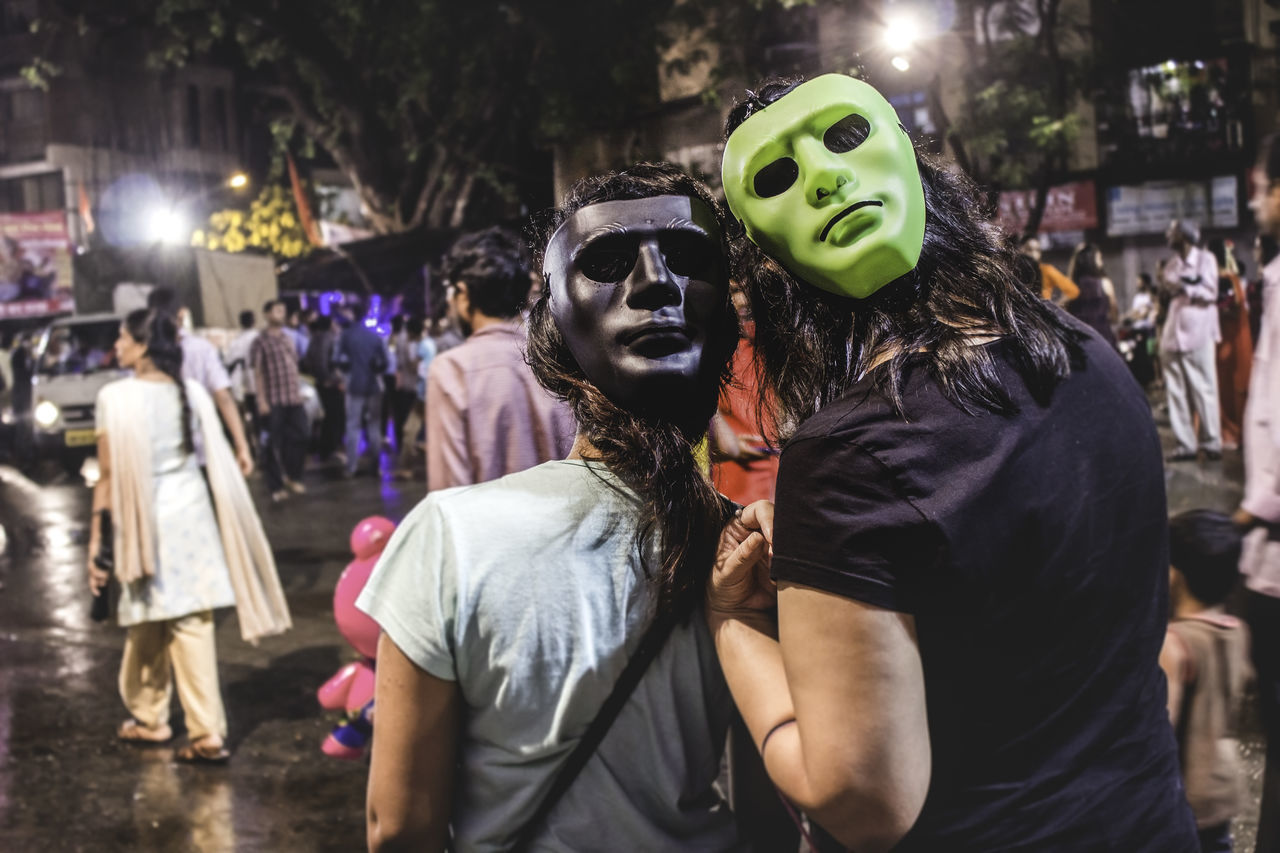 mask - disguise, real people, night, costume, togetherness, enjoyment, men, fun, focus on foreground, leisure activity, celebration, women, disguise, large group of people, lifestyles, performance, outdoors, crowd, halloween, clown, adult, people