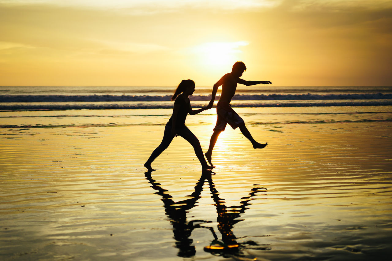 two people, sunset, sea, togetherness, water, leisure activity, silhouette, beach, real people, fun, reflection, lifestyles, full length, nature, horizon over water, scenics, vacations, beauty in nature, standing, sky, enjoyment, outdoors, friendship, bonding, young adult, day