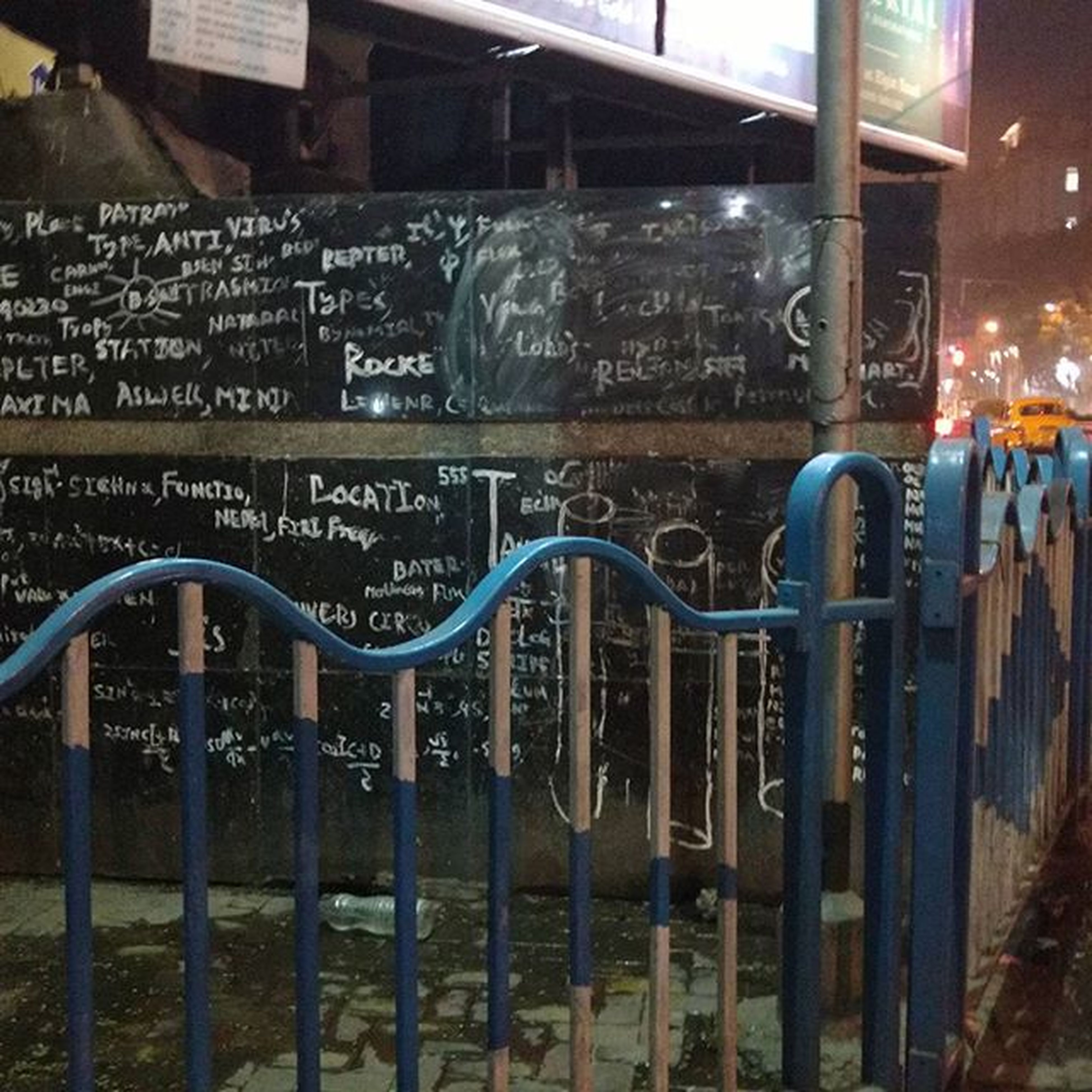 text, western script, built structure, architecture, metal, communication, railing, building exterior, illuminated, city, night, no people, fence, outdoors, metallic, graffiti, security, empty, reflection