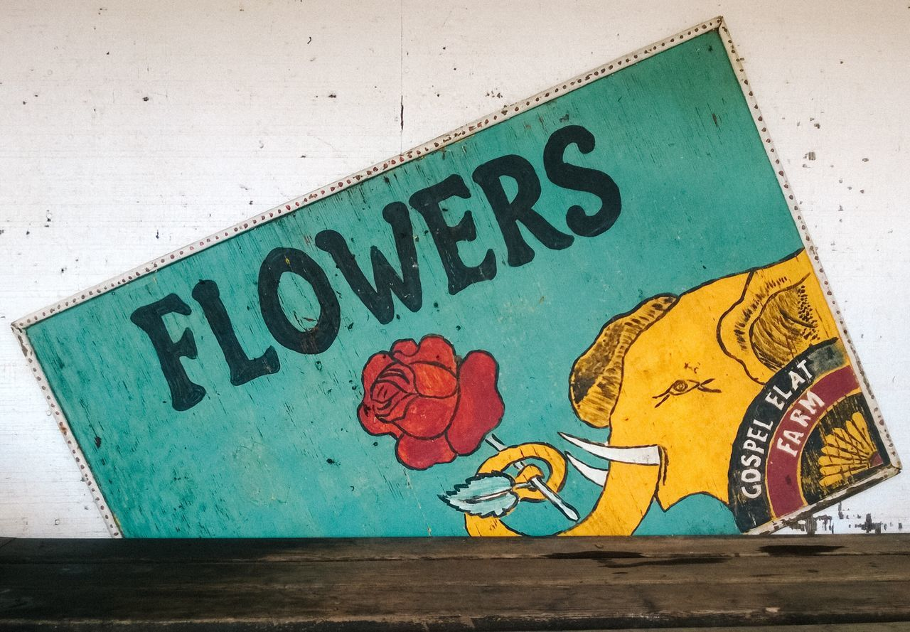 Old flower sign at a farm stand Text Close-up No People Flowers Sign Elephant Antique Handmade Rustic Farm