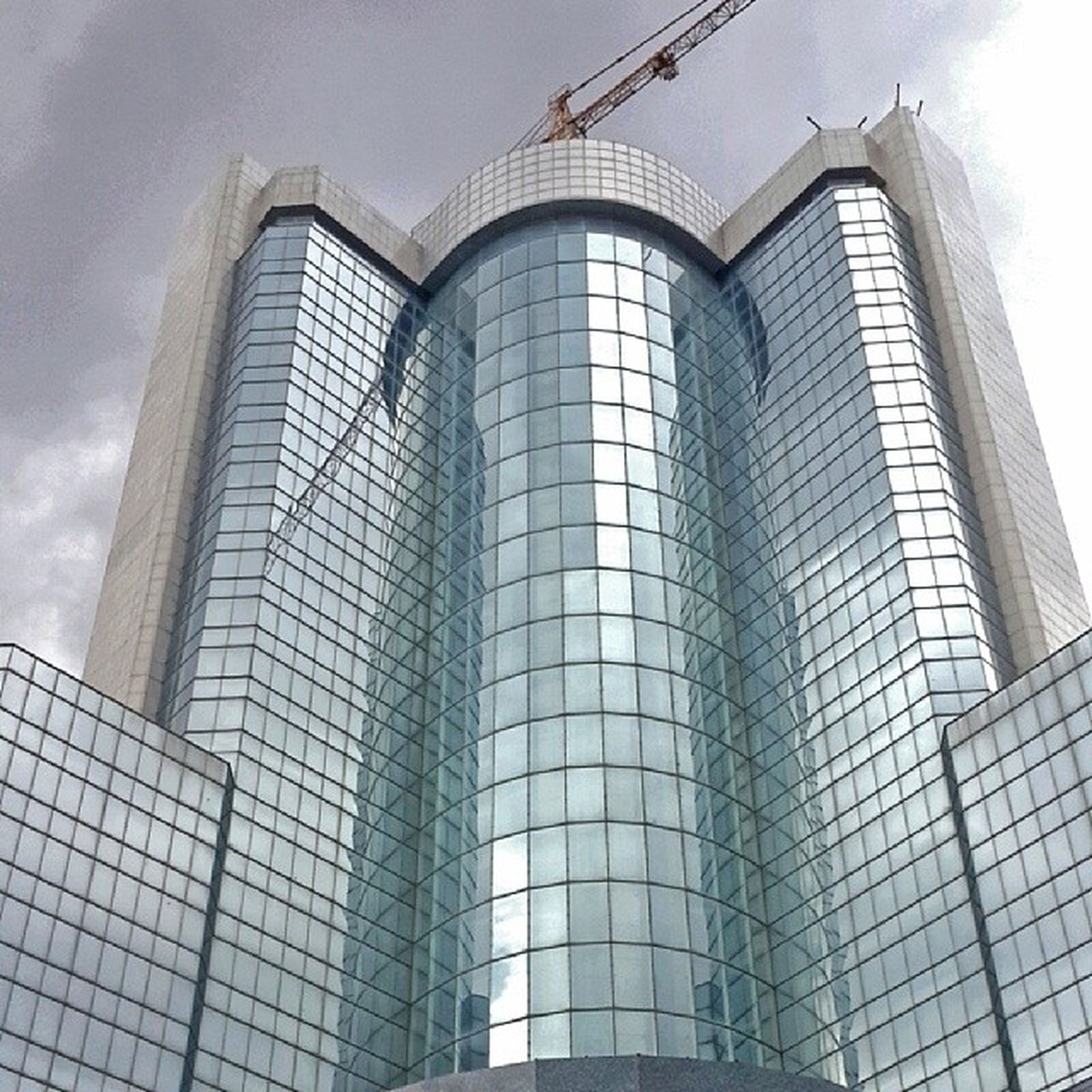 architecture, low angle view, built structure, building exterior, modern, office building, glass - material, sky, city, tall - high, skyscraper, building, window, reflection, tower, architectural feature, no people, day, cloud - sky, outdoors