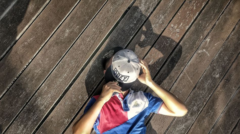 Sleep Lifestyles Real People Human Body Part Adult Human Hand Day Close-up Outdoor Photography OBEY Cap Red And Blue
