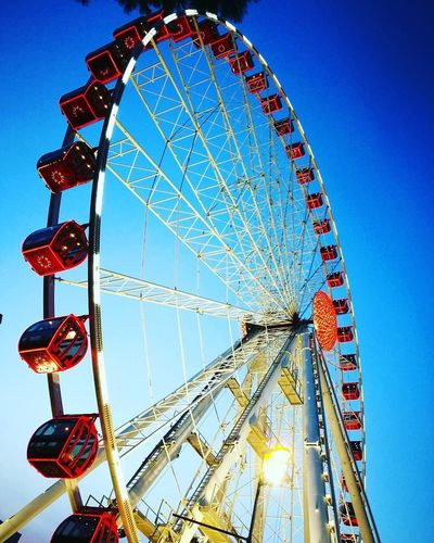 Amusement Park Ferris Wheel Amusement Park Ride Arts Culture And Entertainment Low Angle View Sky Day Outdoors Blue No People Built Structure Clear Sky Red