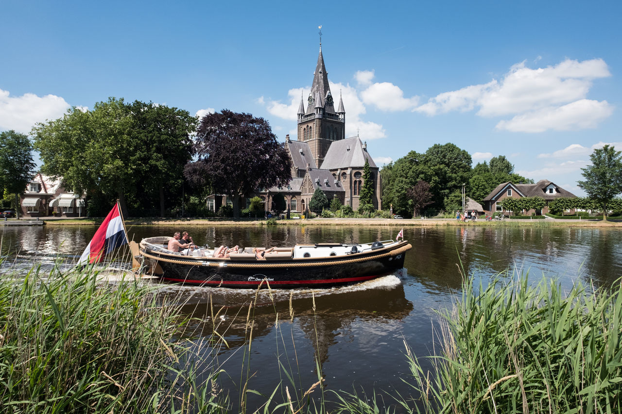 Boat @ Nes a/d Amstel Architecture Beauty In Nature Boat Building Exterior Built Structure Day Flag Grass Nature Nautical Vessel Outdoors Recreational Pursuit Religion River Sky Summer Tree Water Waterfront