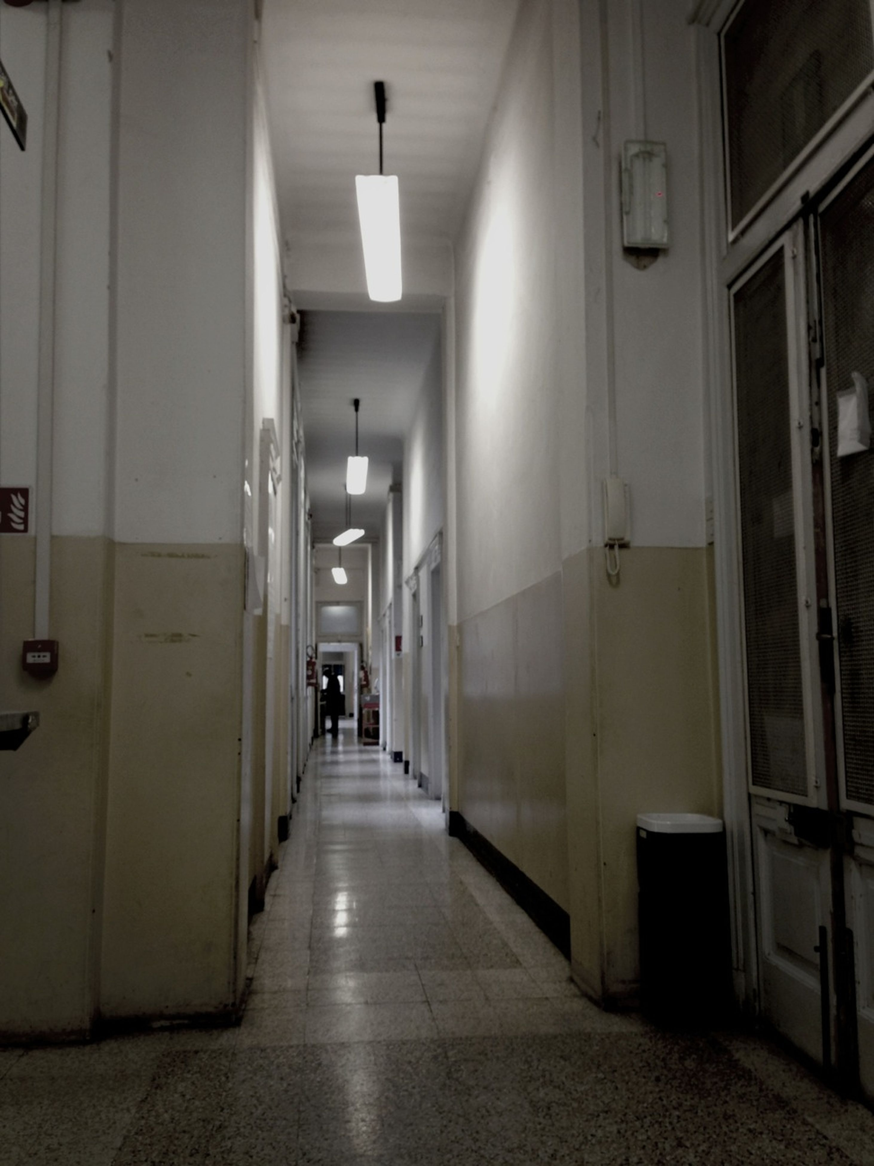 indoors, architecture, built structure, corridor, the way forward, illuminated, lighting equipment, empty, door, diminishing perspective, tiled floor, building, narrow, flooring, wall - building feature, incidental people, absence, building exterior, in a row, vanishing point