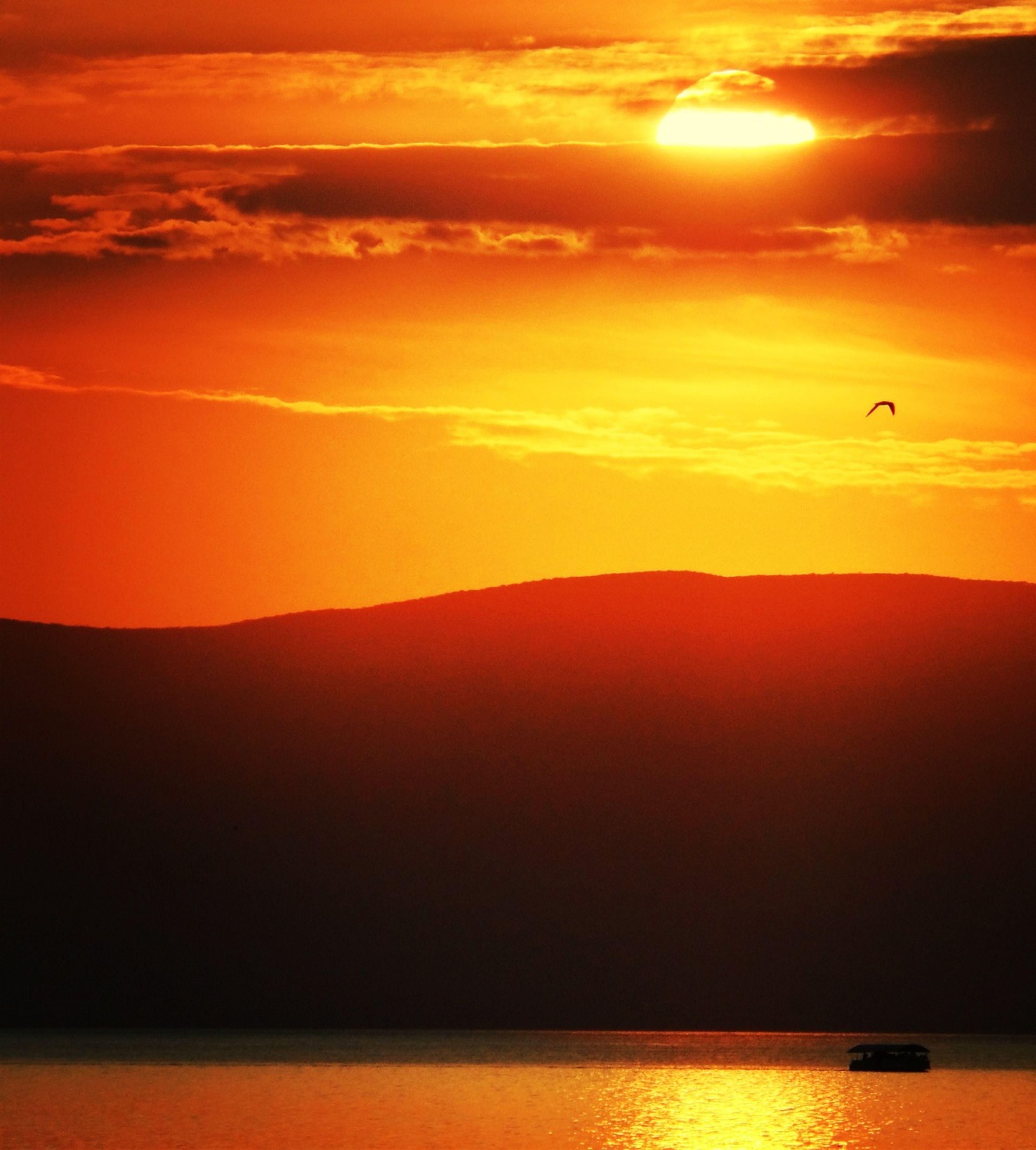 sunset, orange color, scenics, tranquil scene, sun, tranquility, silhouette, beauty in nature, sky, idyllic, mountain, nature, landscape, mountain range, majestic, sunlight, non-urban scene, horizon over land, remote, outdoors