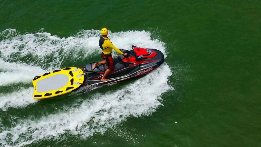 Adventure Lifeguard On Duty Dramatic Lifestyles Pattern Jet Ski Speed Leisure Activity Life Guard Nautical Vessel Life Jacket Motion Activity Sports Helmet Men Wave Summer Copy Space Travel Destinations Yellow Rescue Green Ocean Craft Vivid Real People Breathing Space