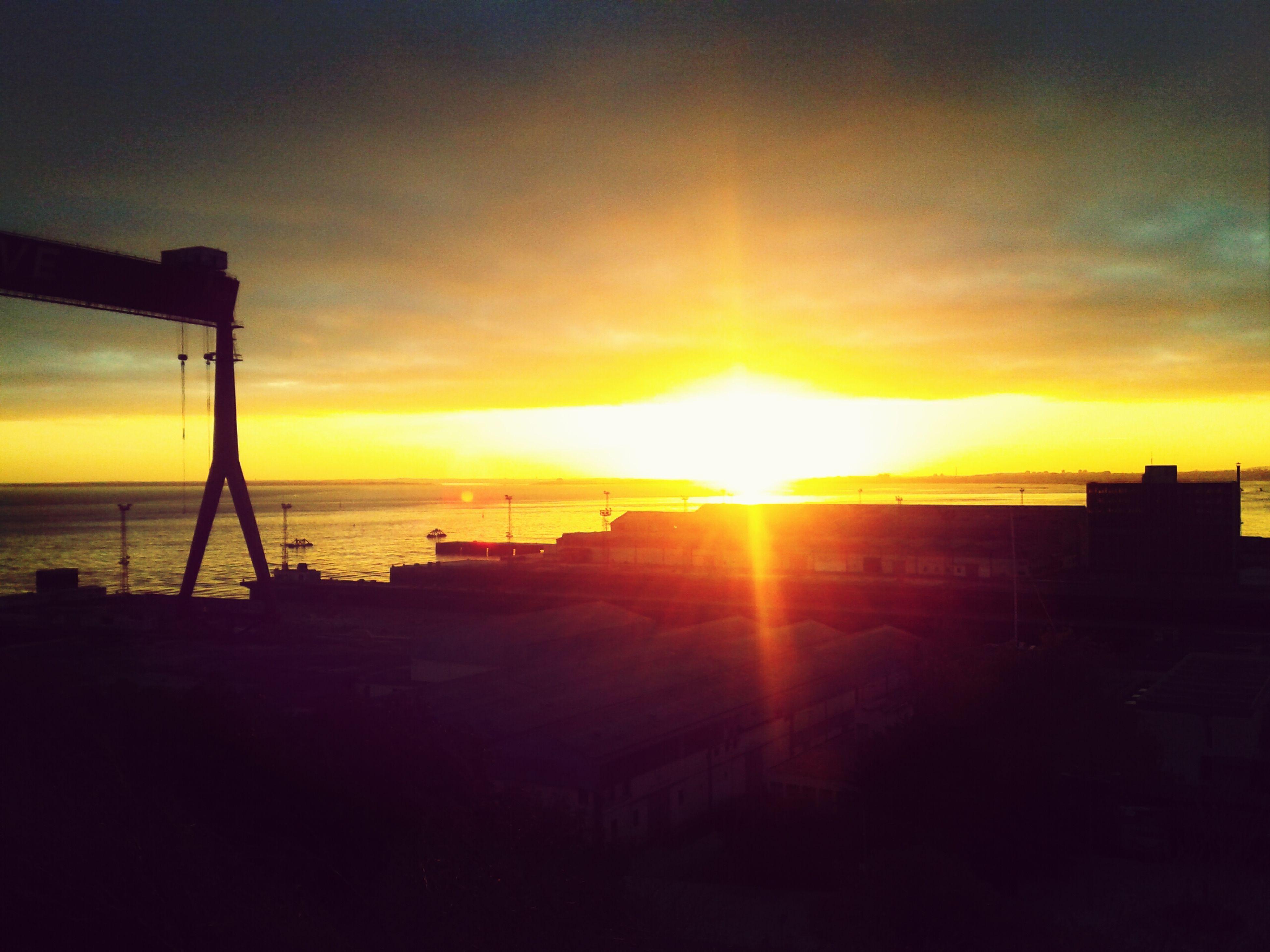 sunset, sun, sea, horizon over water, silhouette, sky, orange color, scenics, water, beauty in nature, sunlight, tranquil scene, tranquility, idyllic, sunbeam, cloud - sky, built structure, nature, architecture, beach