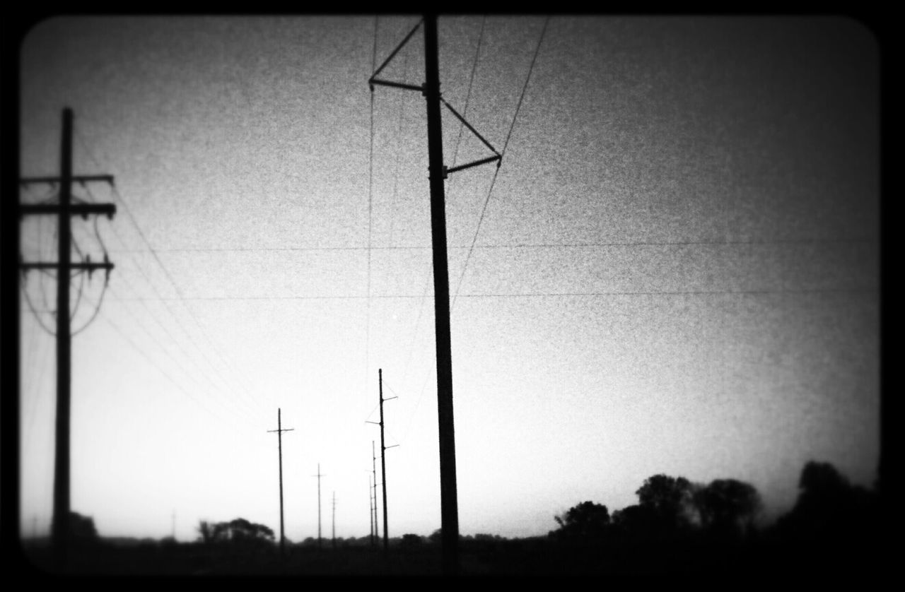 Low angle view of electricity pylons against clear sky