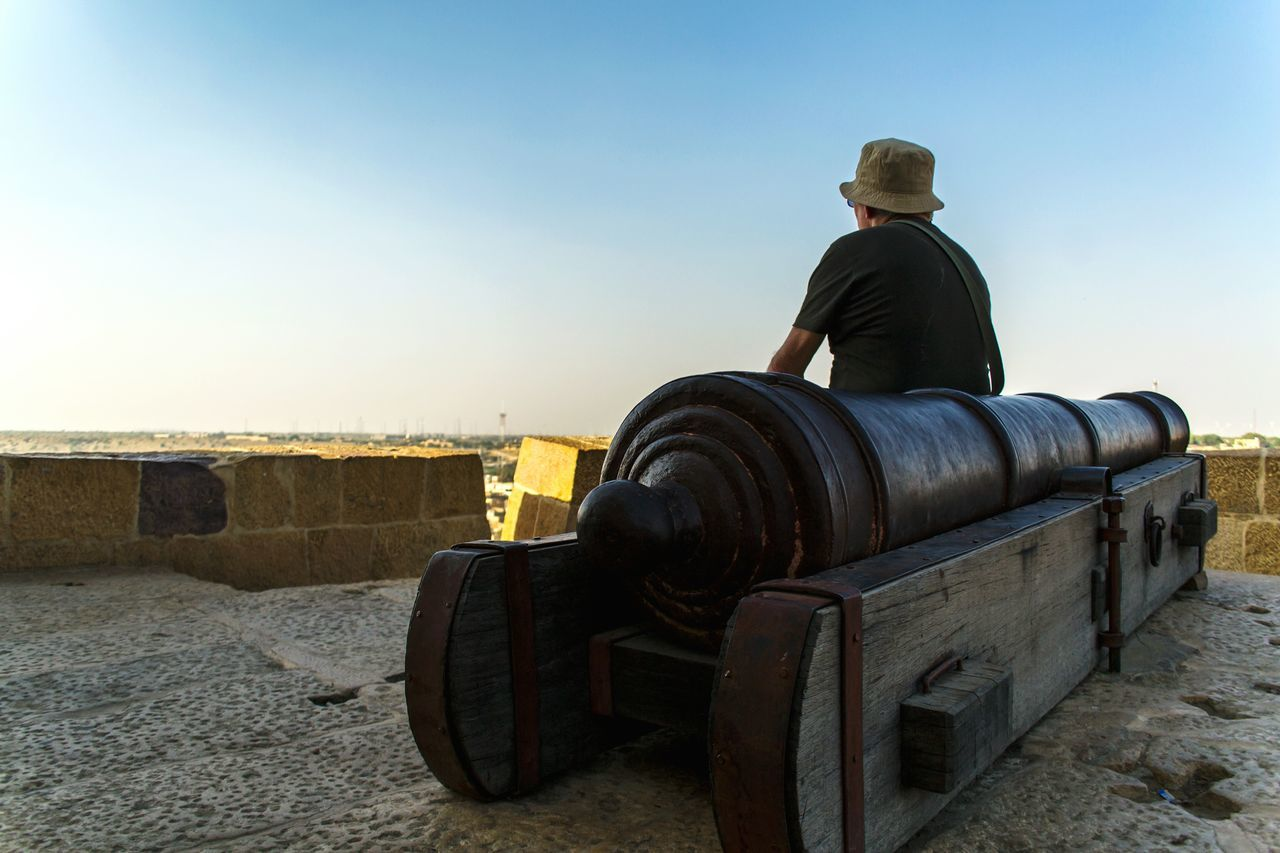 Tourist relaxing and enjoying the city view from the fort..Sitting One Person Adults Only Rear View People Adult One Man Only Only Men Sky Nature Outdoors Beauty In Nature Day Light And Shadow Fort View Hat Sunny Day Cannon Travel Destinations Relaxing What Who Where