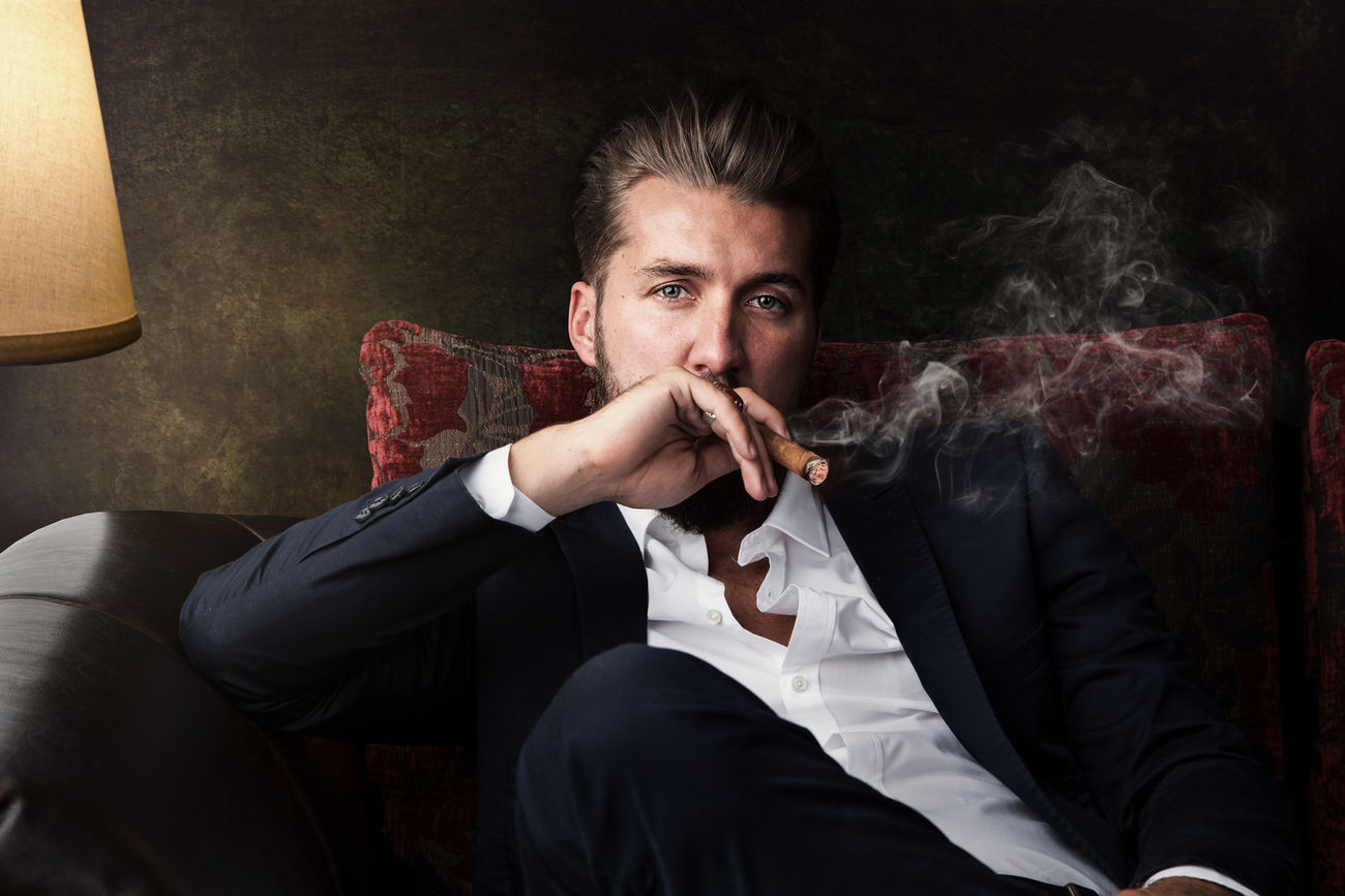 Portrait of an attractive business man with a cigar Attractive Background Beard Black Boss Brown Businessman Chair Cigar Face Fashion Handsome Lamp Lifestyle Light Mafia  Model One People Person Portrait Sitting Smoke Successful Vintage