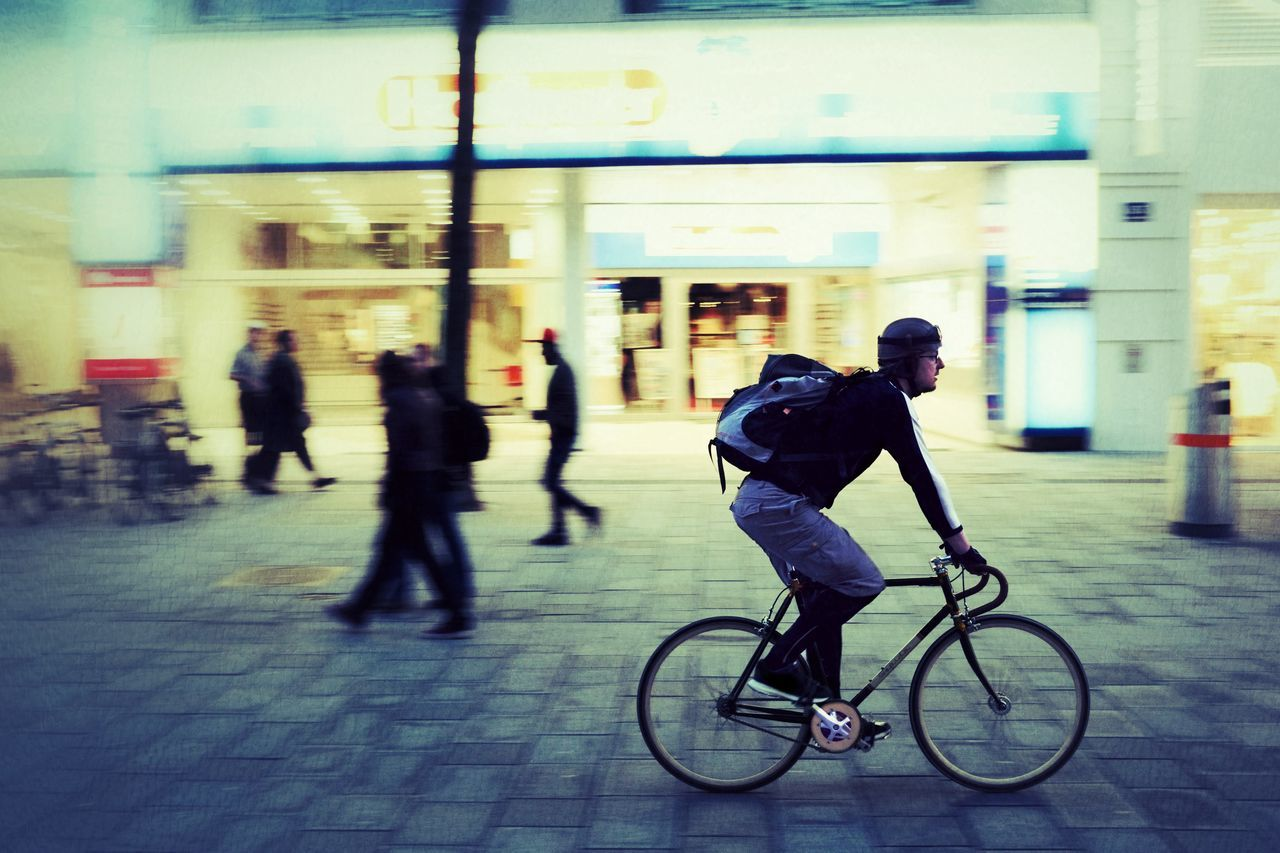 men, real people, bicycle, motion, full length, blurred motion, transportation, lifestyles, women, day, built structure, outdoors, one person, architecture, city, people