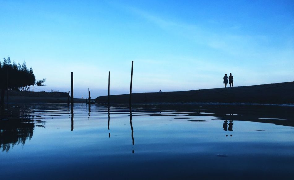 DONGSHAN ISLAND- 旅志 Silhouette Reflection Water Tranquility Tranquil Scene Blue Scenics Lake Waterfront Standing Wooden Post Outline Nature Calm Beauty In Nature Cloud Day Standing Water Outdoors Sky