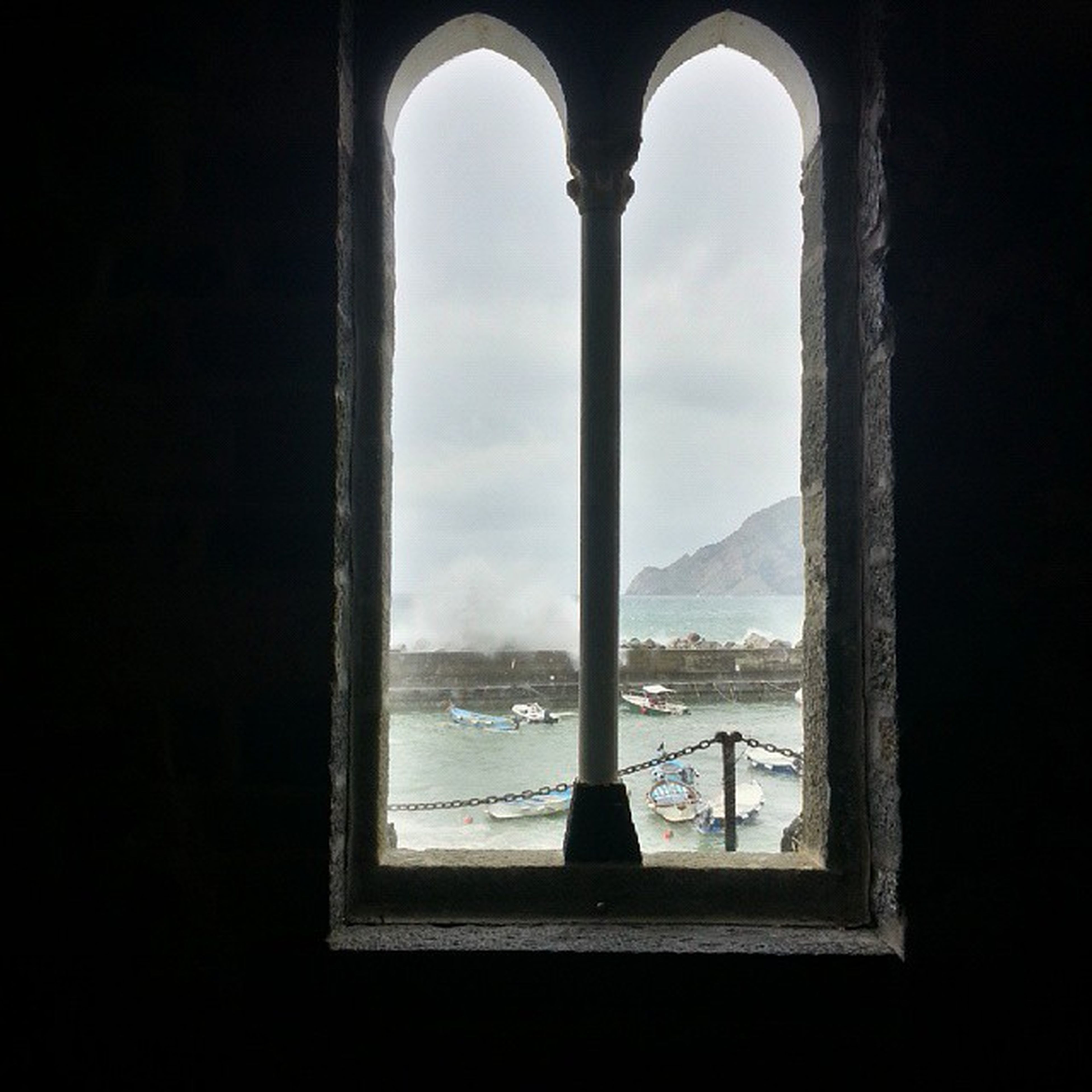 indoors, window, water, sky, built structure, architecture, mountain, glass - material, transparent, looking through window, day, arch, nature, tranquility, silhouette, sea, no people, reflection, lake, scenics