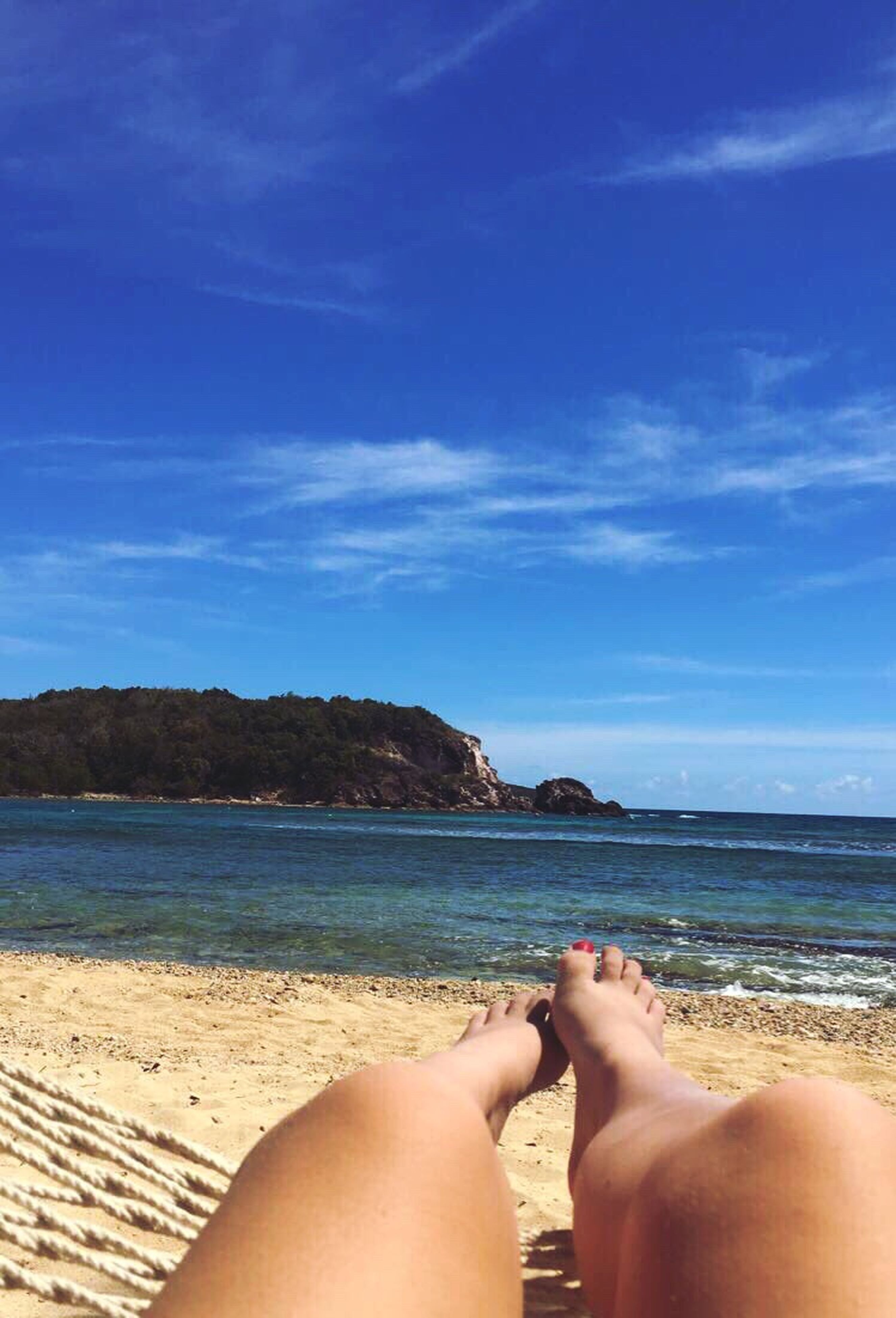 beach, low section, human leg, sea, one person, sand, sky, barefoot, water, personal perspective, human body part, real people, day, nature, cloud - sky, outdoors, leisure activity, blue, scenics, lifestyles, beauty in nature, relaxation, horizon over water, close-up, human hand, adult, people