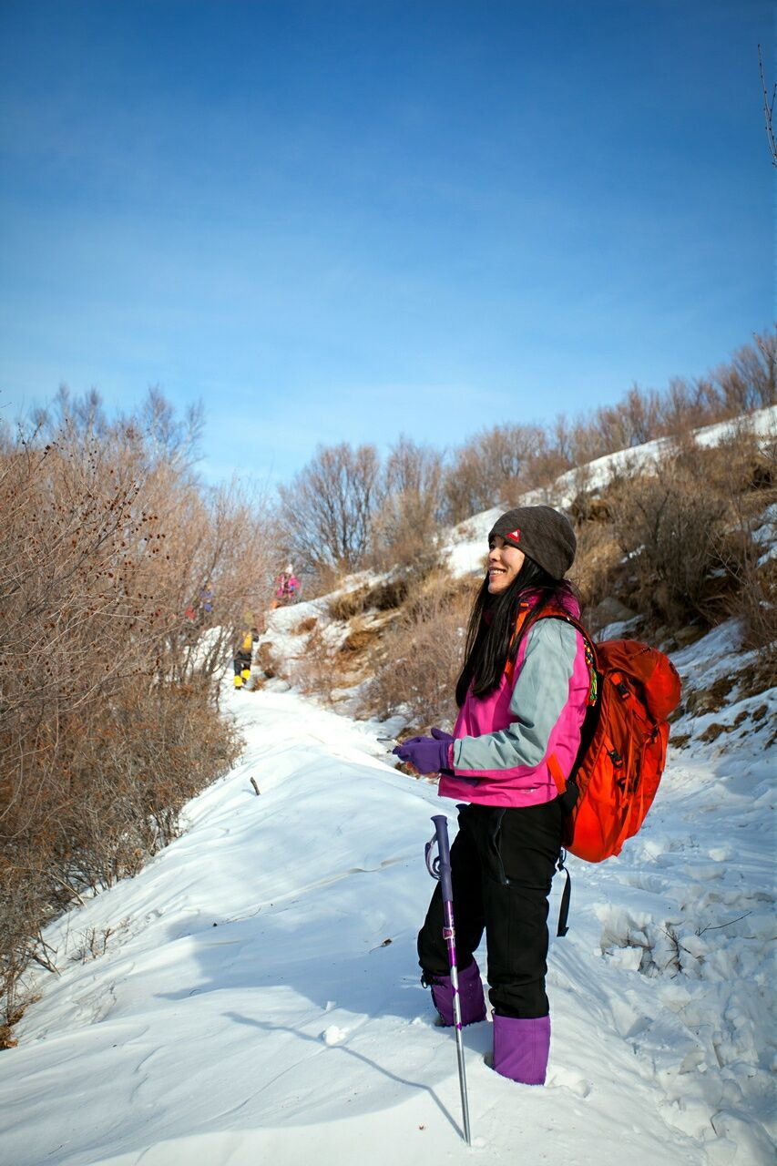 real people, winter, cold temperature, snow, one person, full length, leisure activity, lifestyles, nature, outdoors, warm clothing, day, backpack, standing, beauty in nature, sky, vacations, clear sky, bare tree, adventure, landscape, tree, young adult, people