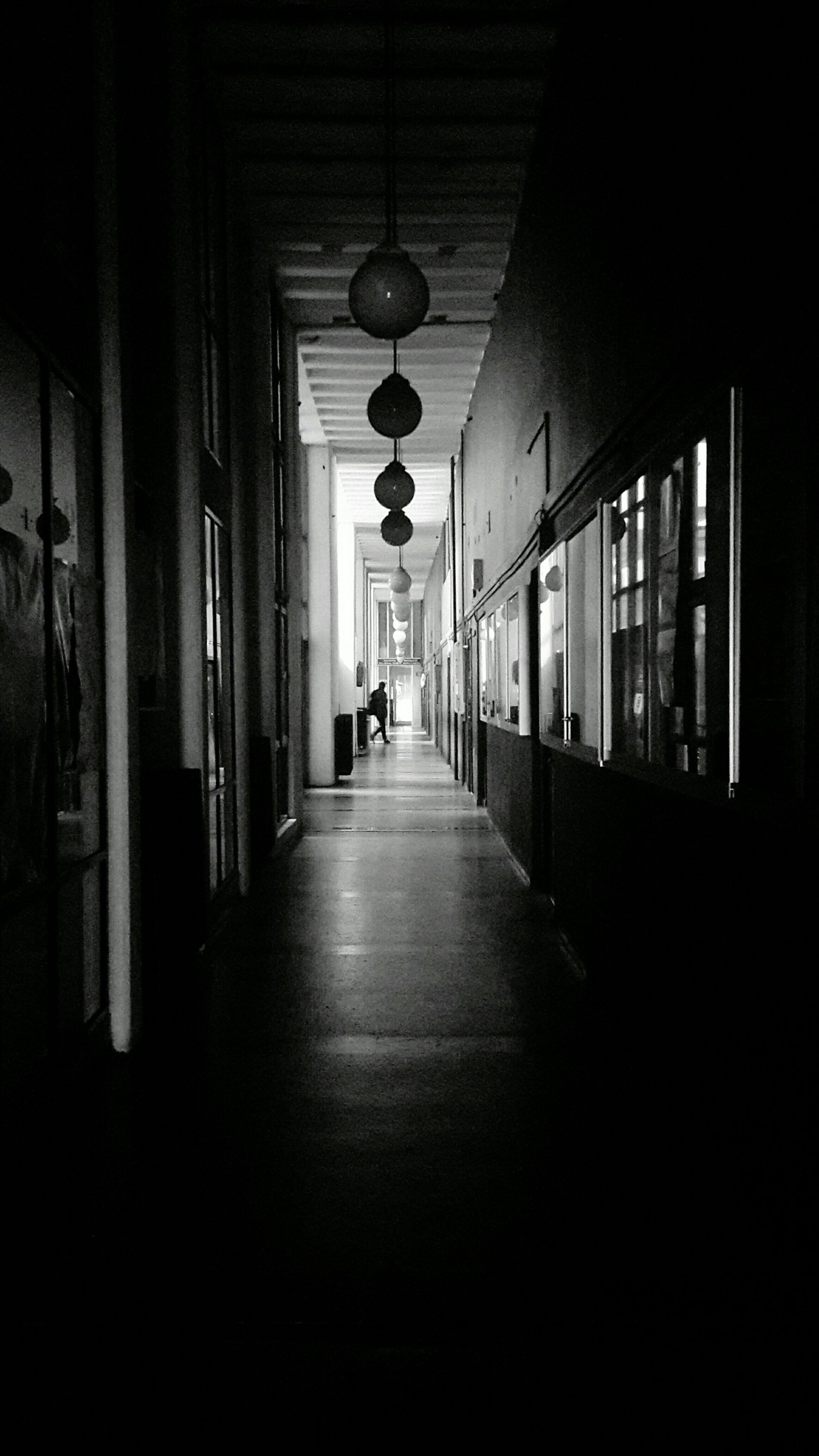 indoors, architecture, the way forward, corridor, built structure, illuminated, lighting equipment, diminishing perspective, ceiling, empty, building, window, in a row, incidental people, vanishing point, electric lamp, narrow, flooring, building exterior, long