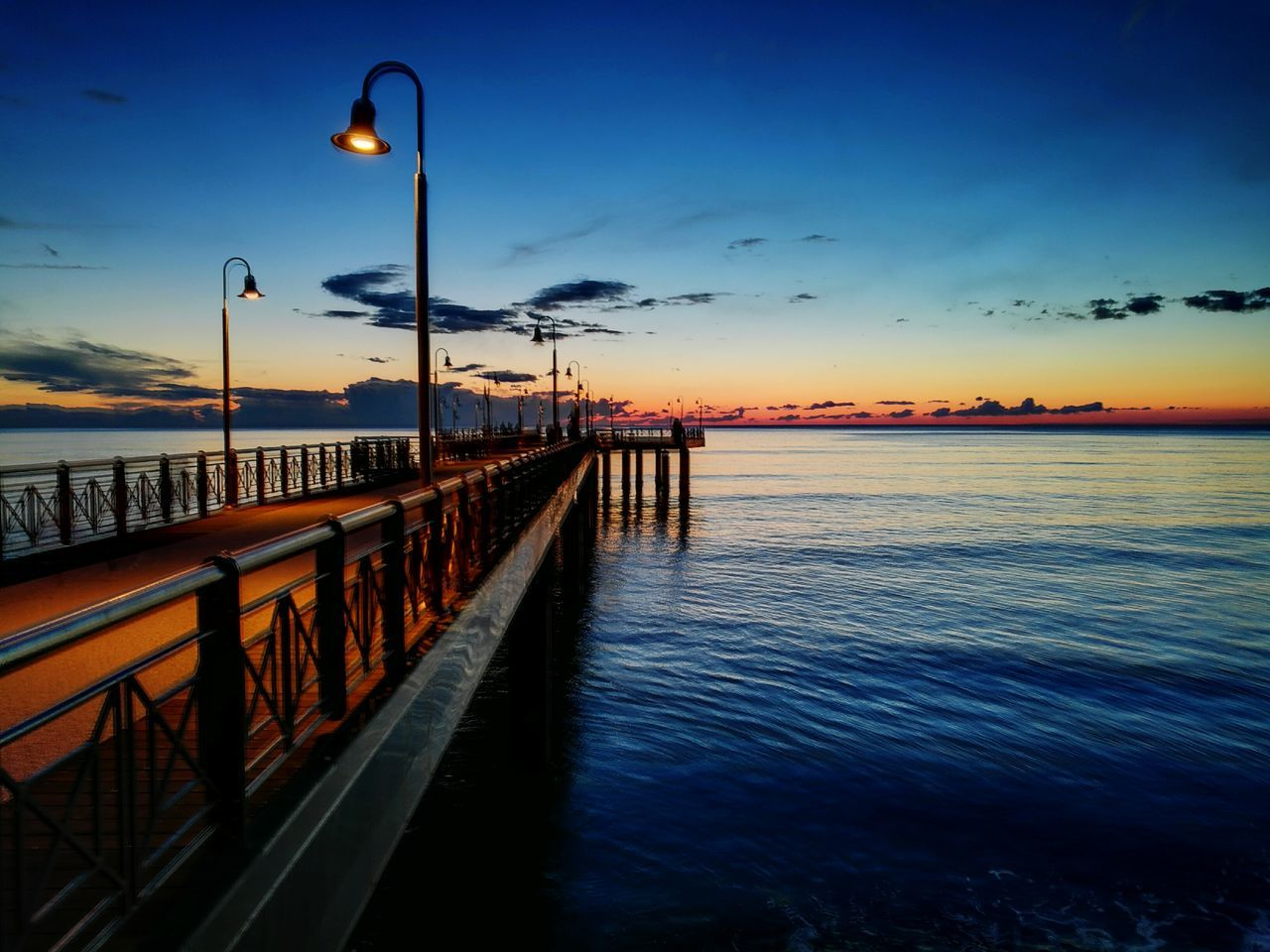 sea, sunset, water, sky, street light, nature, tranquil scene, lighting equipment, outdoors, beauty in nature, scenics, cloud - sky, tranquility, horizon over water, blue, illuminated, no people, built structure, travel destinations, architecture, day
