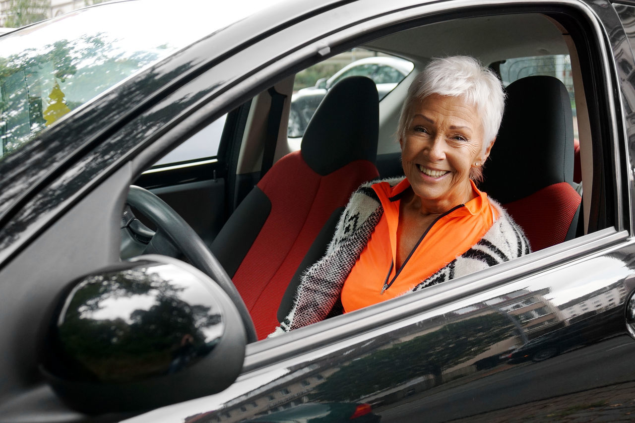 Adult Best Ager Car Compact Car Driver Elderly Female Lifestyles Mature Mode Of Transport Motorist Person Senior Small Car Street Transportation Travel White Hair Window Woman The Drive