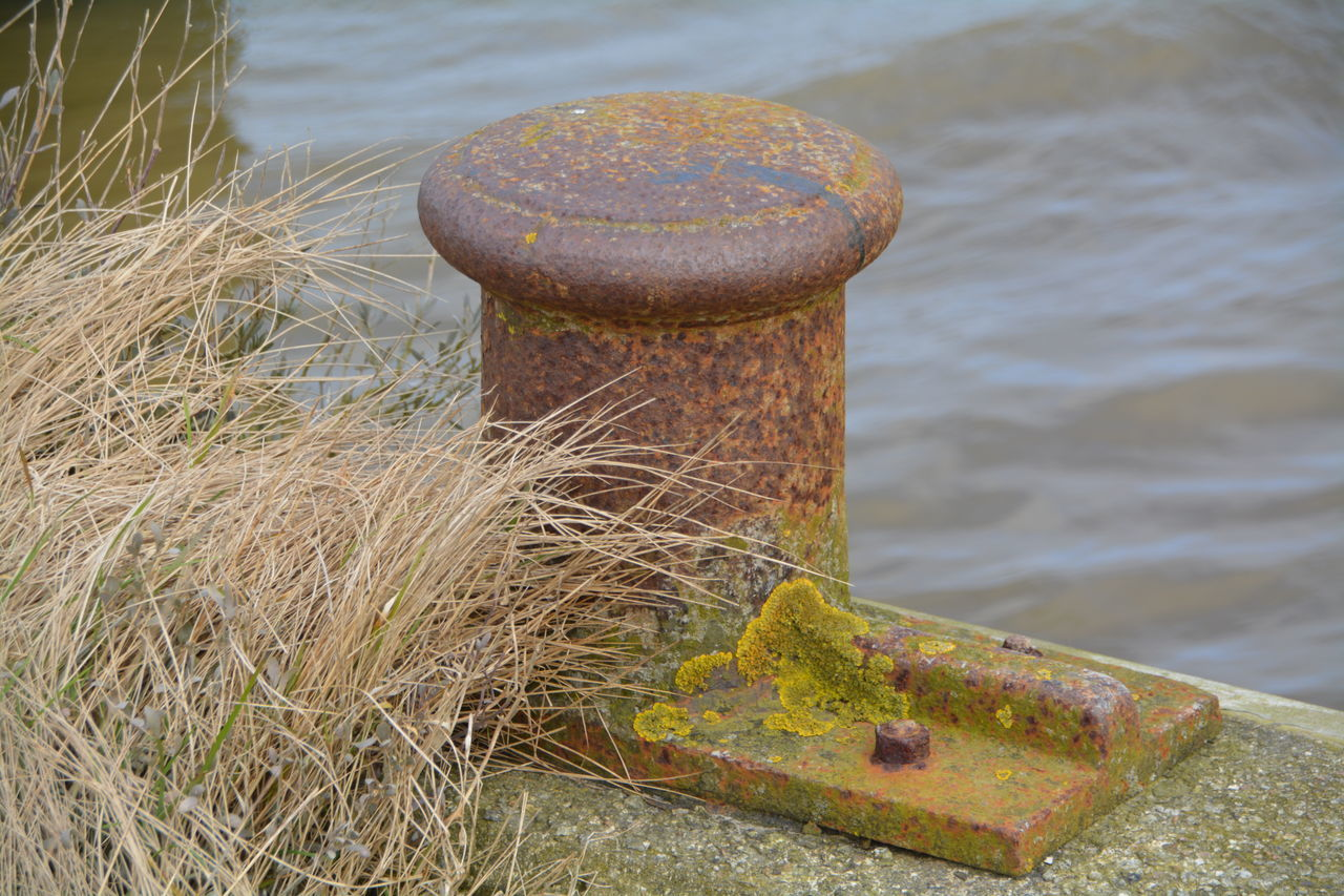 High Angle View Of Rusty Bollard By River
