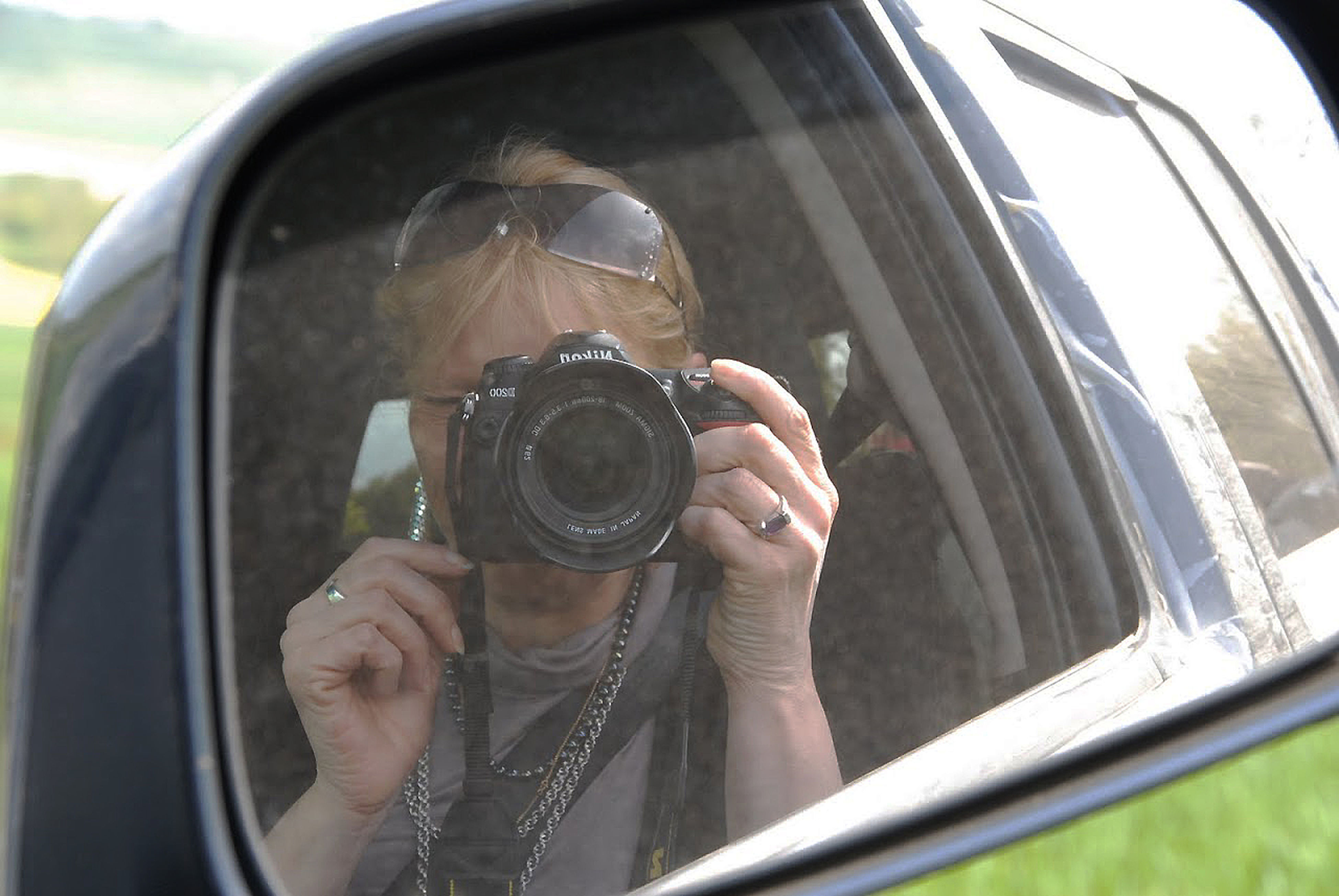 transportation, mode of transport, land vehicle, car, photography themes, part of, holding, lifestyles, vehicle interior, travel, photographing, close-up, car interior, cropped, leisure activity, camera - photographic equipment, reflection, side-view mirror